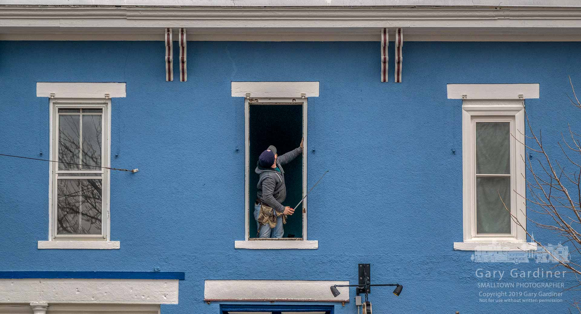 An installer checks dimension on a second-floor apartment window before replacing it with a double-pane window duringthe renovation of parts of the building just south of College Ave. on State Street in Uptown Westerville. My Final Photo for Feb. 15, 2019.