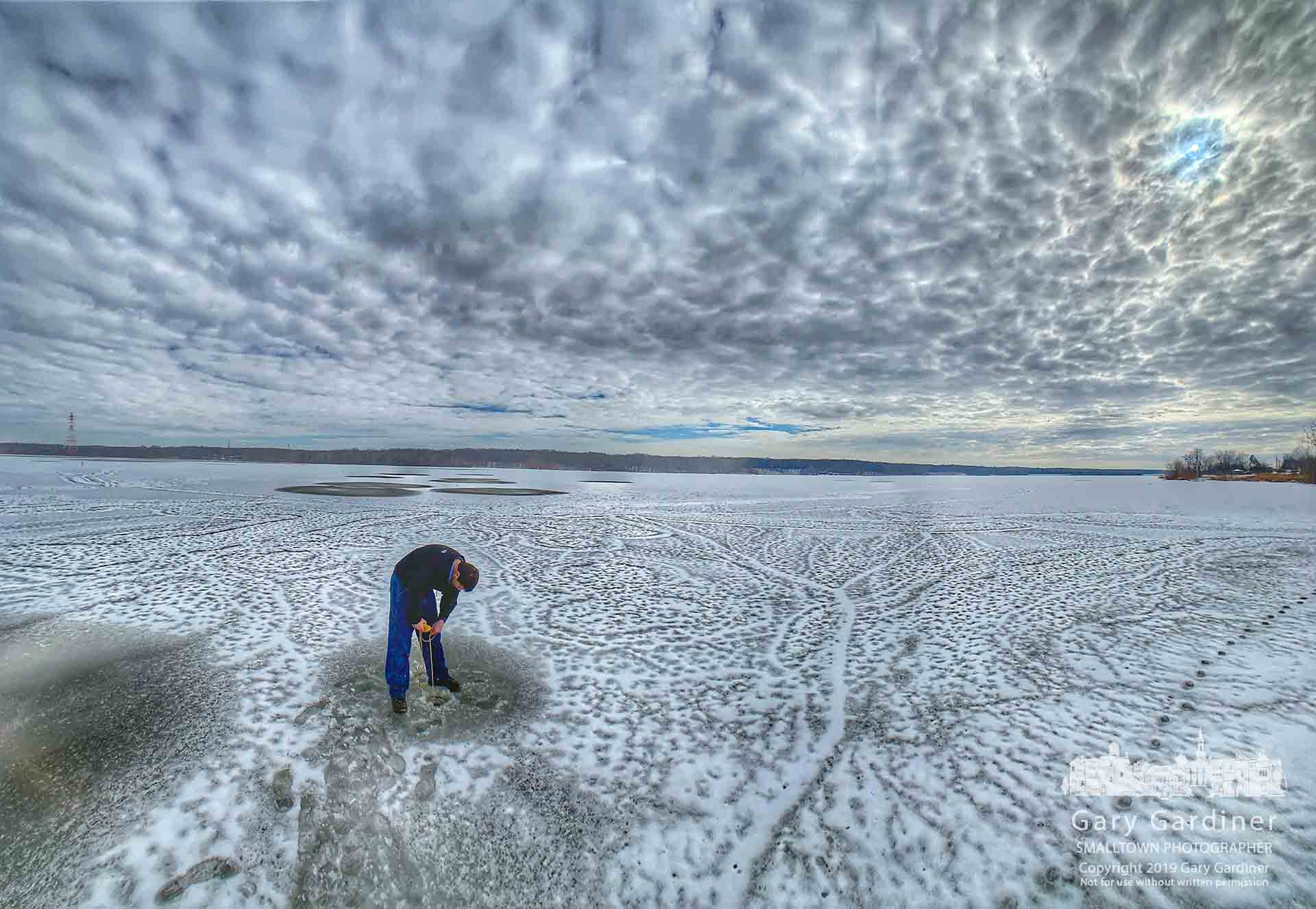 A man drops a super magnet through a hole he punched in the ice at Hoover hoping to retrieve a magnet he lost in an earlier attempt at magnet fishing off the Walnut boat ramp. My Final Photo for Feb. 3, 2019.