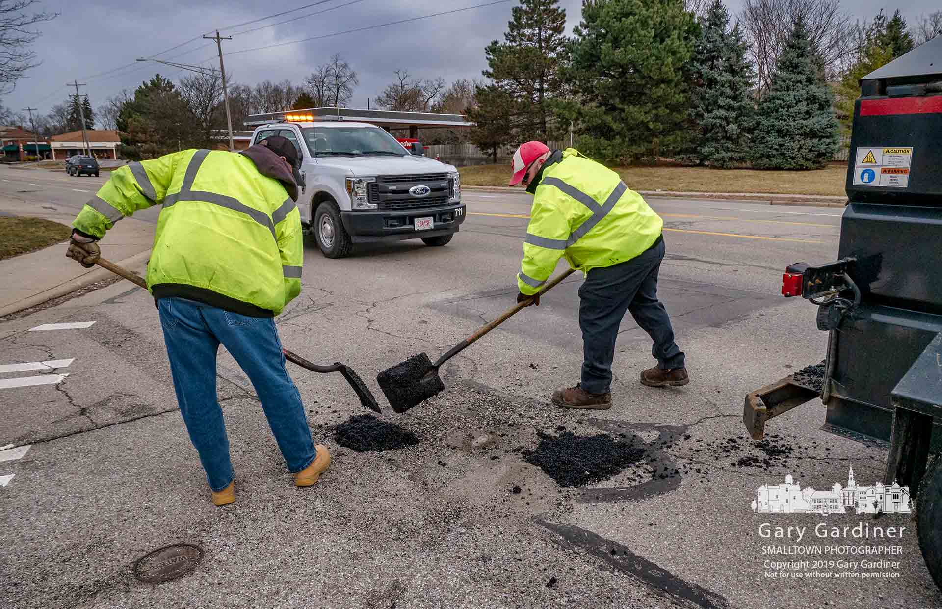 A city crew fills the latest collection of potholes disturbing traffic and cups of coffee on State Street in Westerville. My Final Photo for Feb. 8, 2018.