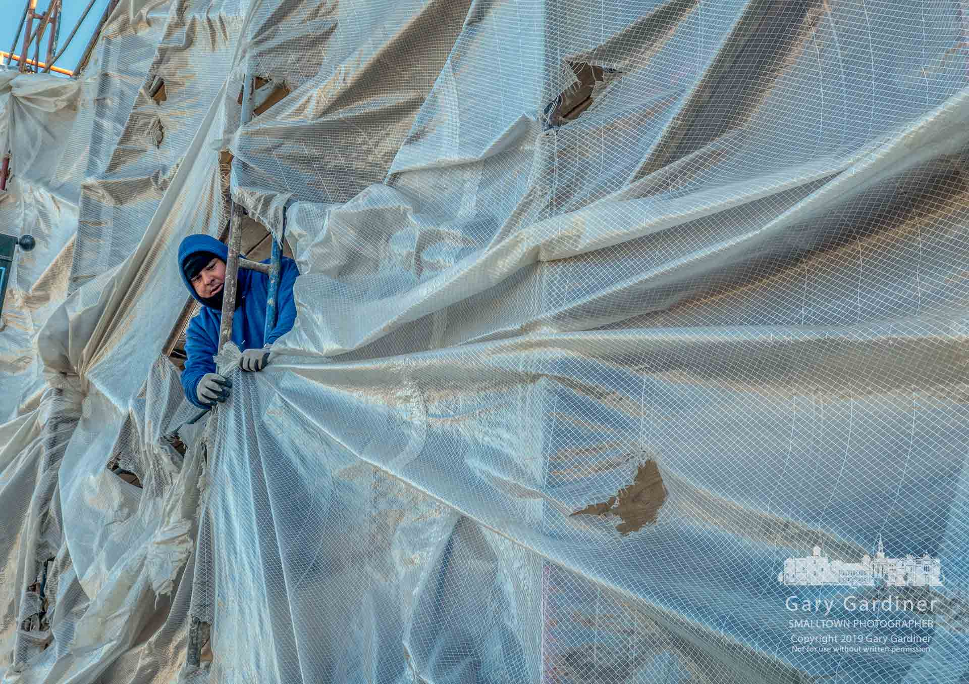 A construction worker temporarily reattaches plastic sheeting to the scaffolding used to as a platform to restore the brickwork and windows at a business on North State Street in Uptown Westerville. My Final Photo for Feb. 25, 2019.