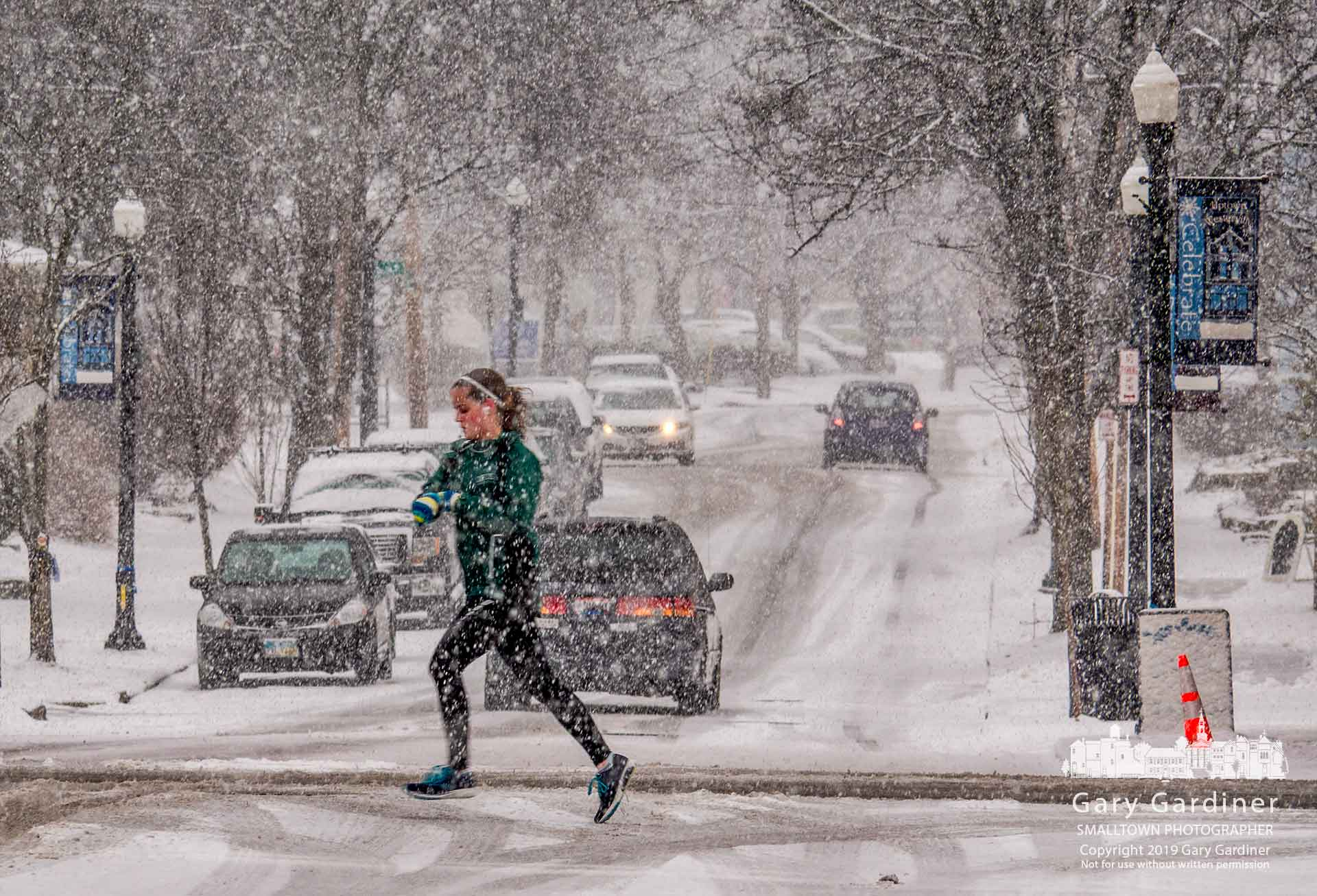 A woman checks her wrist as she crosses College Avenue in Uptown during an afternoon run during heavy snow on Sunday afternoon. My Final Photo for Feb. 10, 2019.
