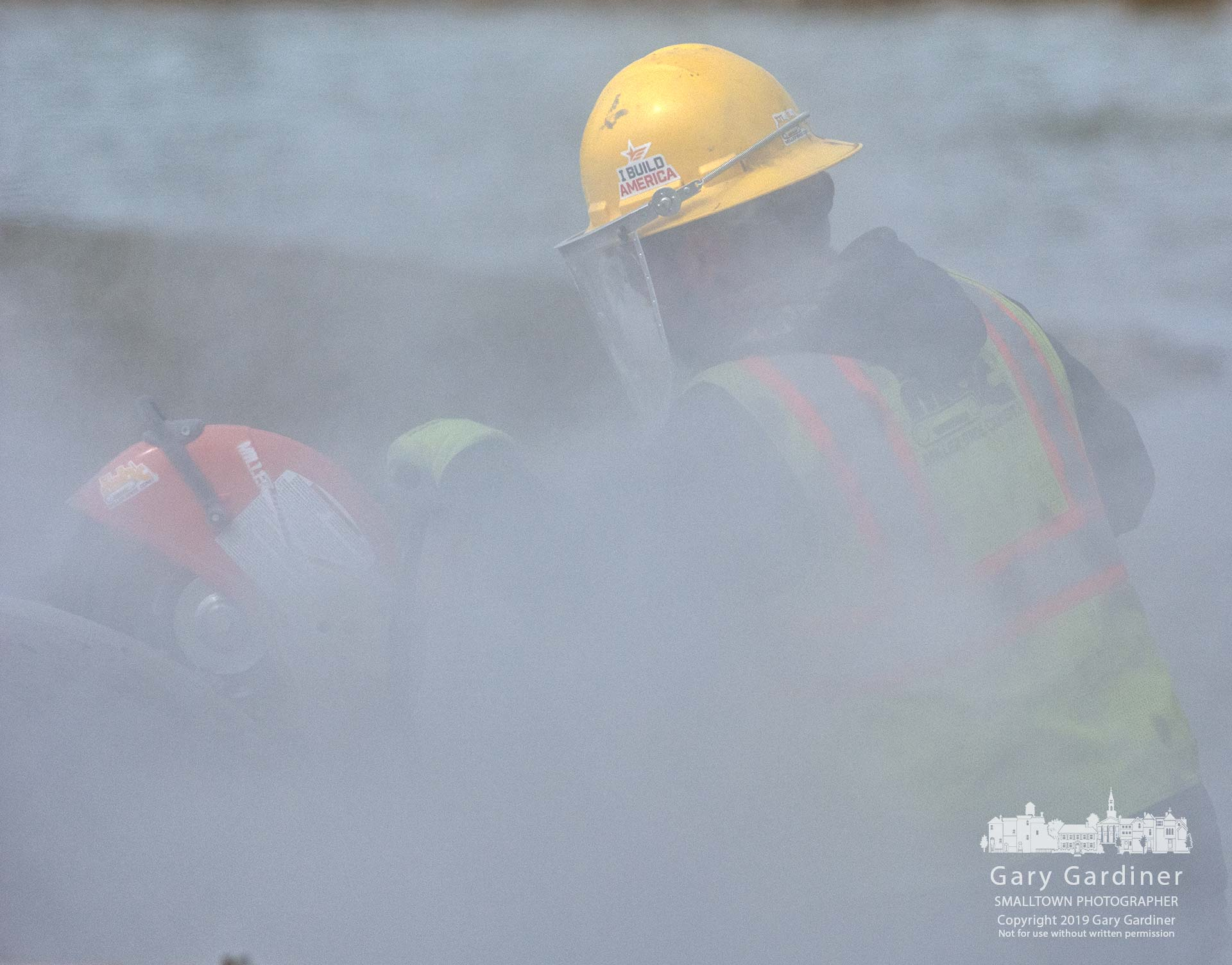 A construction worker is obscured by a cloud of concrete dust as he cuts a section of storm sewer pipe as the city extends Altair Parkway near the DHL building construction site. My Final Photo for March 11, 2019.