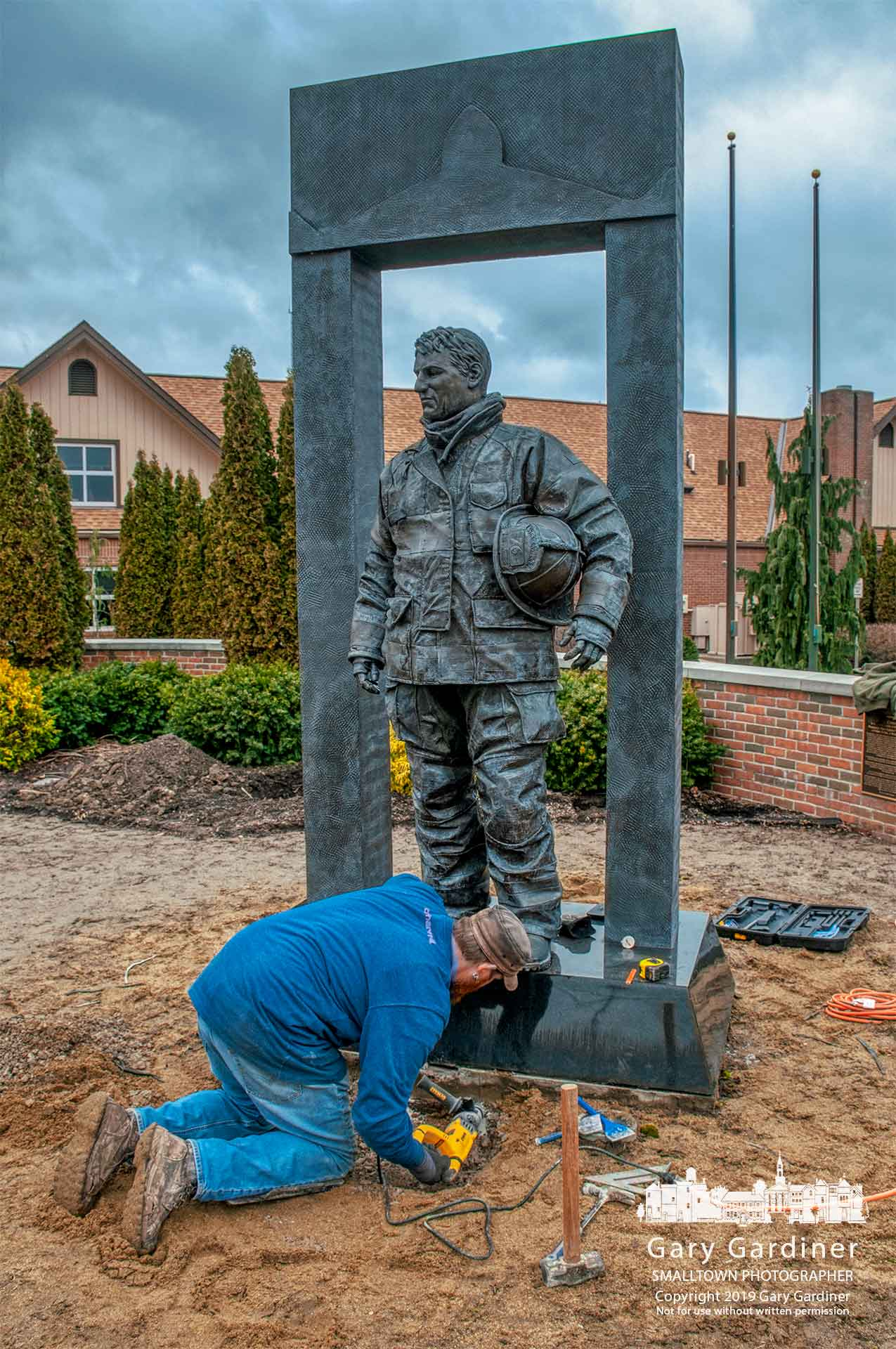 "A worker begins the process for moving ""The Crossing"" firefighter statue from its mount in First Responders Park as the city parks department begins construction of a new park adding the names of two police officers who were killed in 2018. My Final Photo for March 22, 2019."