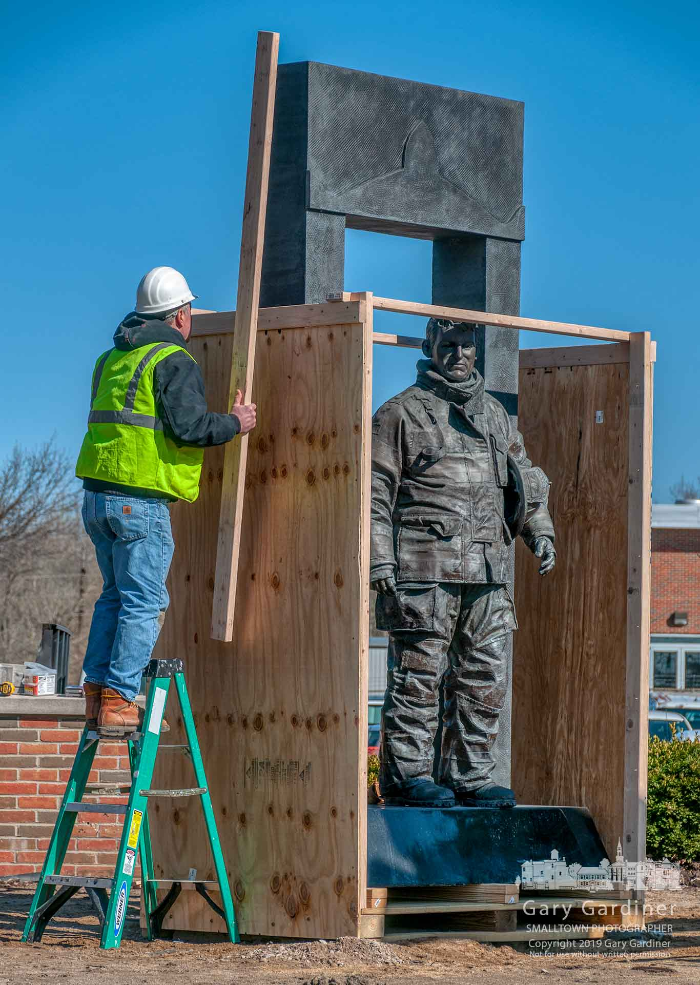 "The firefighter memorial ""The Crossing"" at First Responders Park is covered with a protective wooden covering before it was moved into nearby storage as the park is rebuilt to add memorials to two police officers killed in 2018. My Final Photo for March 26, 2019."