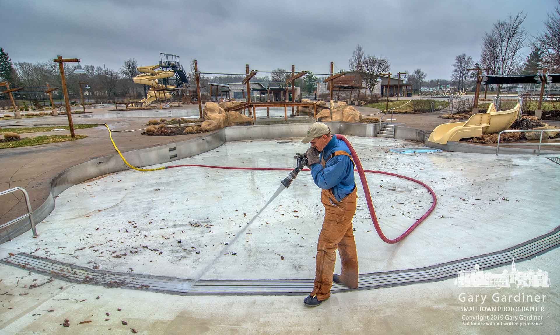 A work crew hoses away the winter dirt and grime from the pools at Highlands as the city prepares to open it about two weeks early this summer. My Final Photo for March 29, 2019.