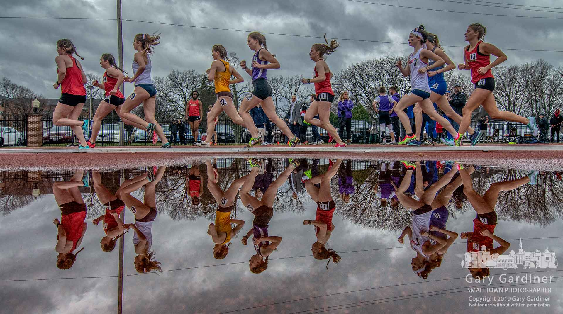 Runners round the first turn in the 5K at the Otterbein April Fools Invitational where runners navigated their way through track and field events with rain during parts of the afternoon. My Final Photo for March 30, 2019.
