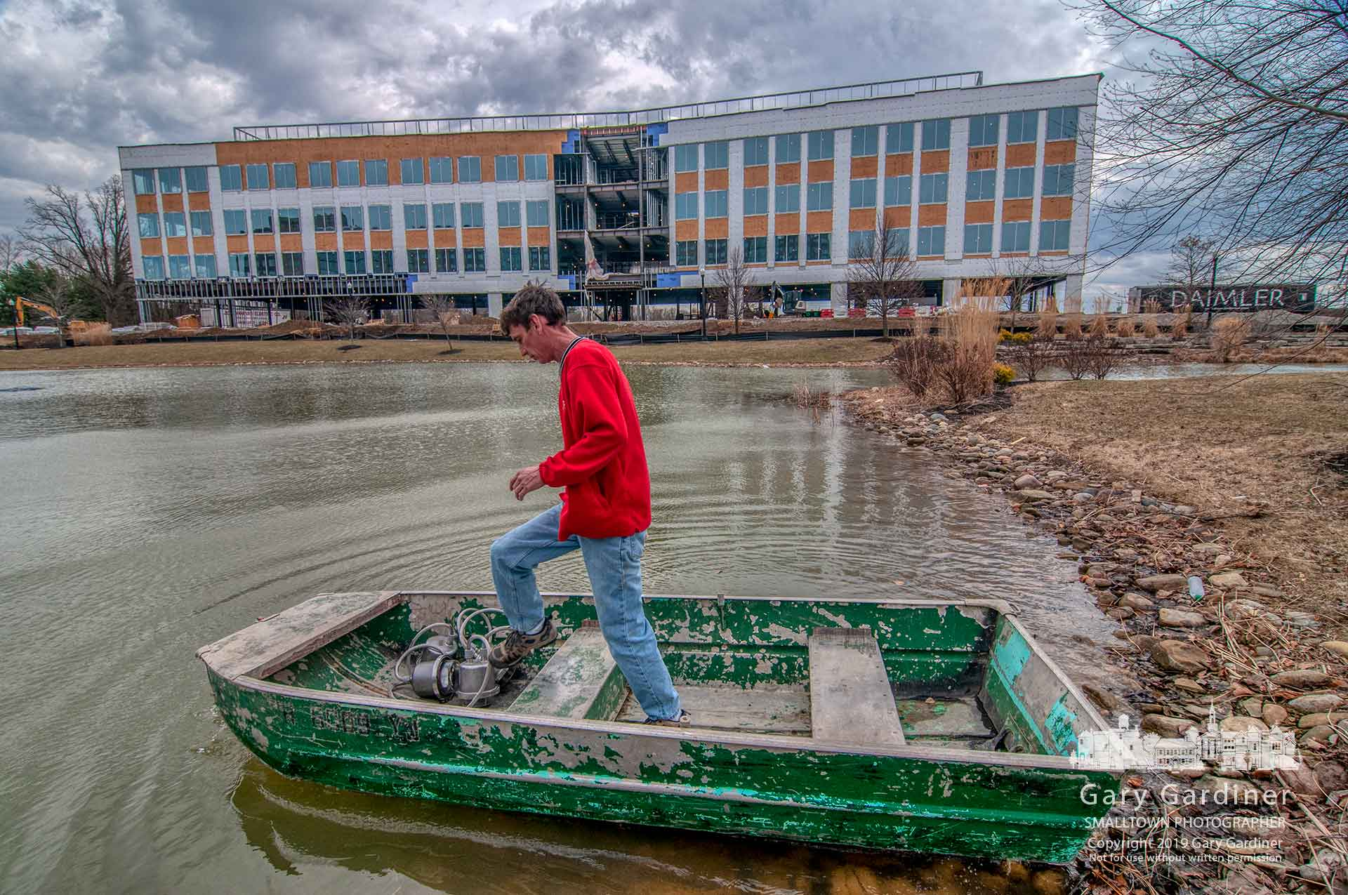 An electrician steps to the bow of his flat-bottom boat where he stores the new LED lights he will install at the fountain in the holding pond between the Renaissance Hotel and the new DHL building under construction at Westar. My Final Photo for March 14, 2019.
