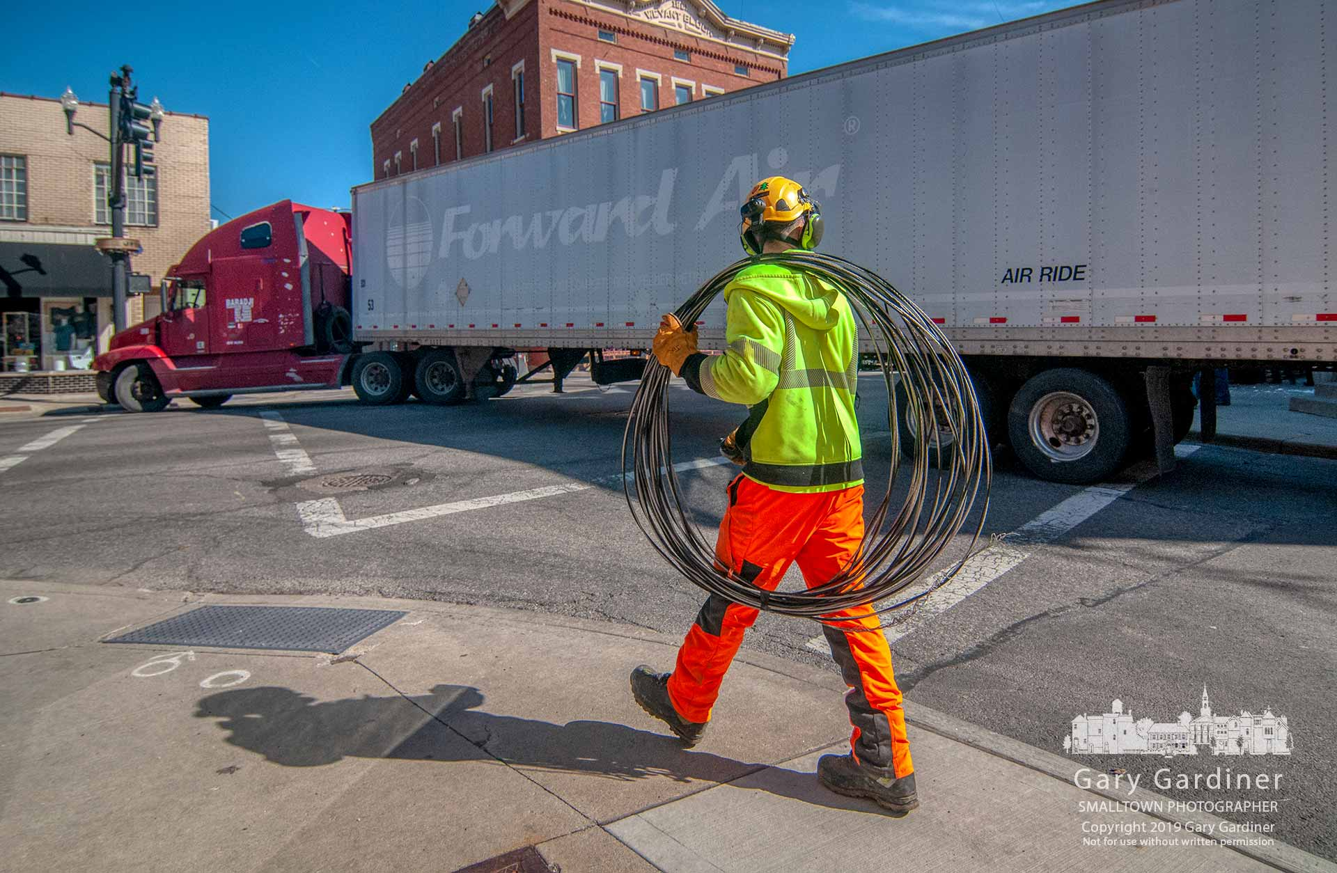 A city electric worker carries away a low-hanging power cable torn from its anchor when it was struck by a truck turning onto State Street damaging the traffic signal and closing the street for several hours for repairs. My Final Photo for March 12, 2019.