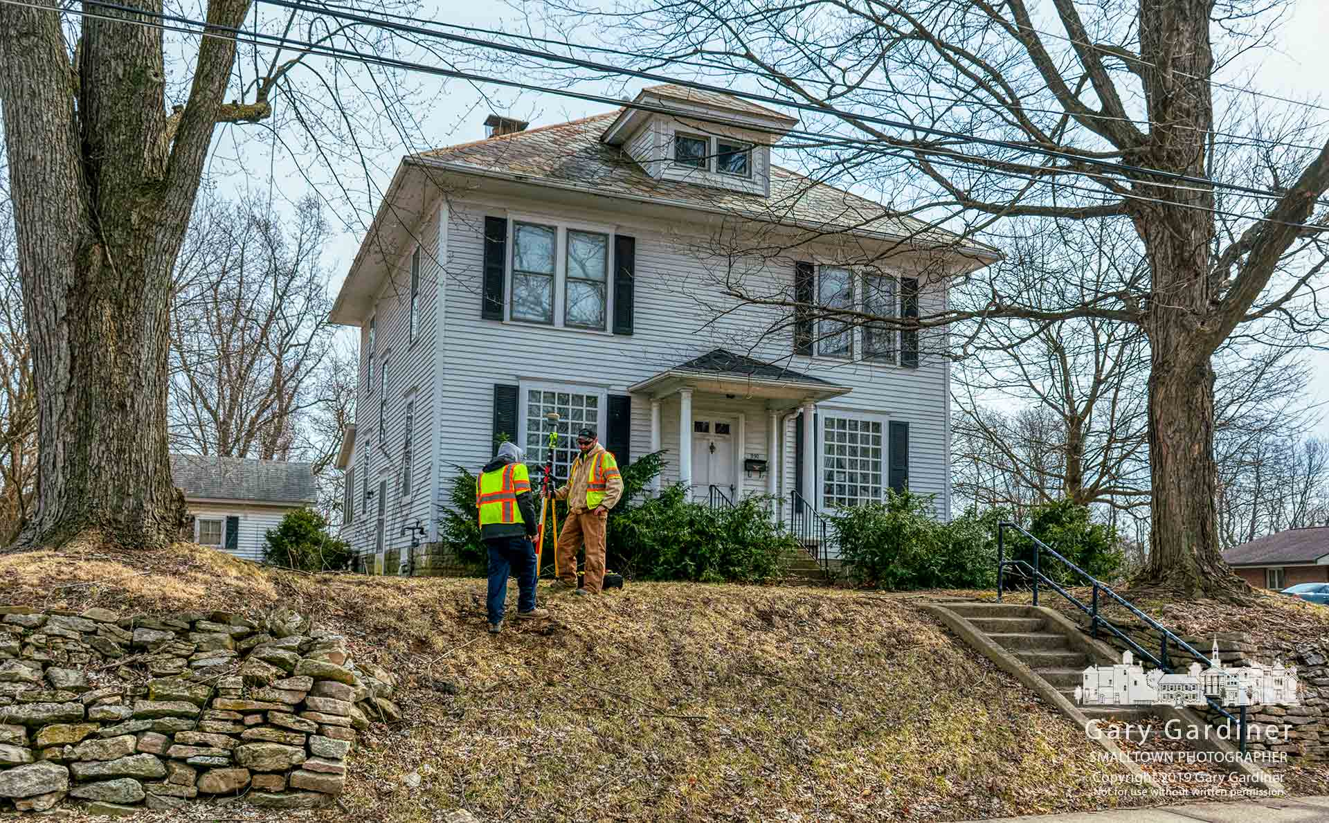 Surveyors mark the location of underground natural gas lines leading to two houses on South State Street where a developer was approved to demolish the buildings, clear the property of trees, and build an office and apartment complex. My Final Photo for March 20, 2019.