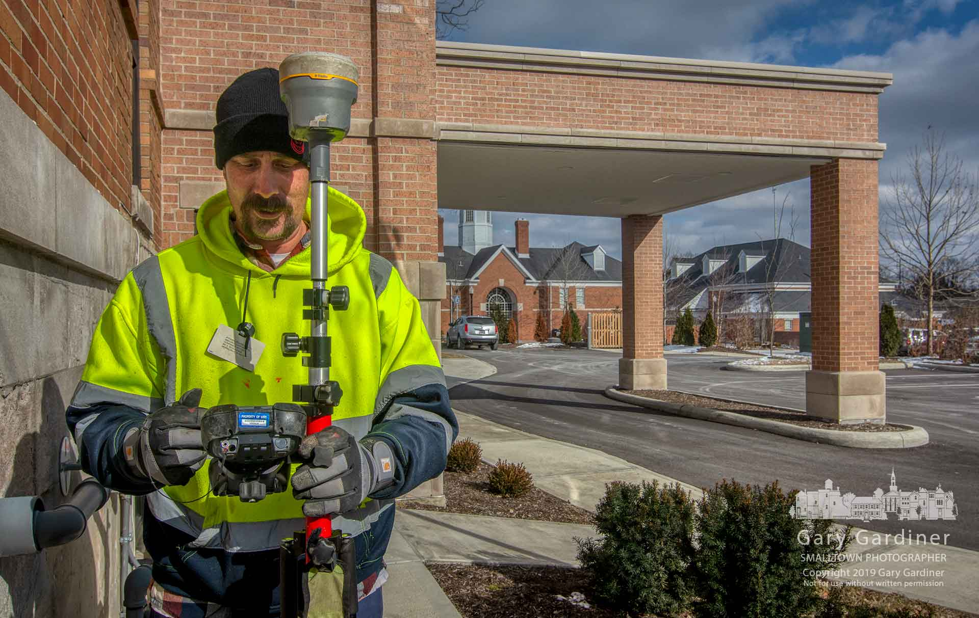 A surveyor uses a GPS system to mark the location of gas lines under streets and leading to structures in Uptown Westerville as Columbus Gas prepares to upgrade sections of its service. My Final Photo for March 6, 2019.
