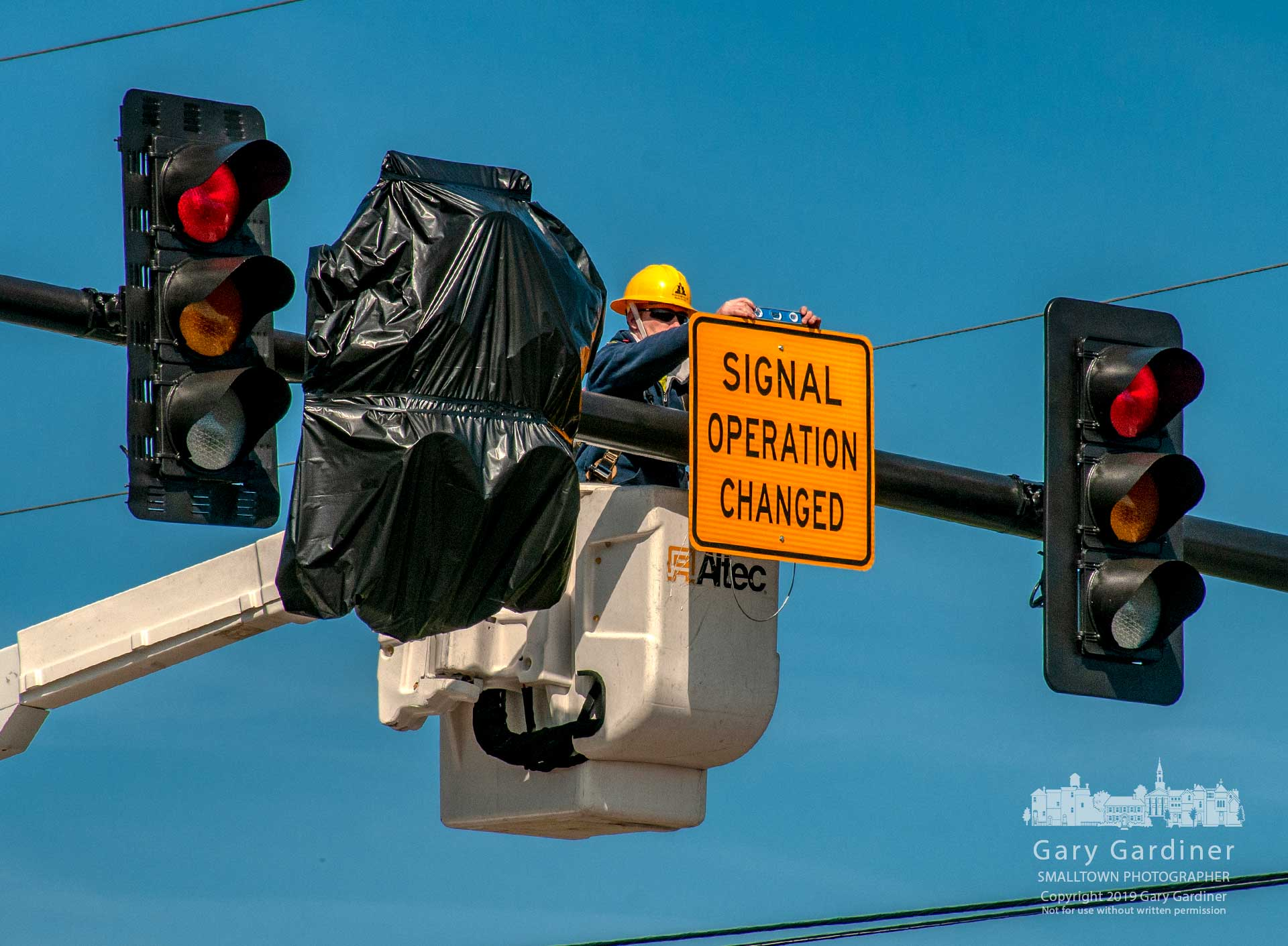 A city electrician levels a sign noting the change of signals set for later this week at County Line road and Africa Road adding left turn signals. My Final Photo for April 1, 2019.