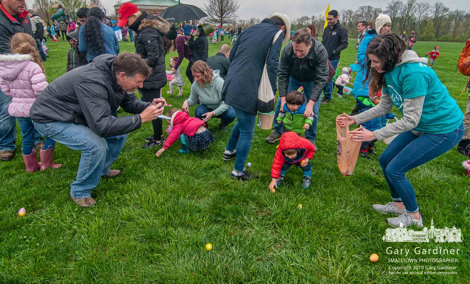 Parents assist and photograph their toddler stumbling across the sports field looking for plastic eggs in the annual hunt in Westerville on Easter weekend. My Final Photo for April 20, 2019.