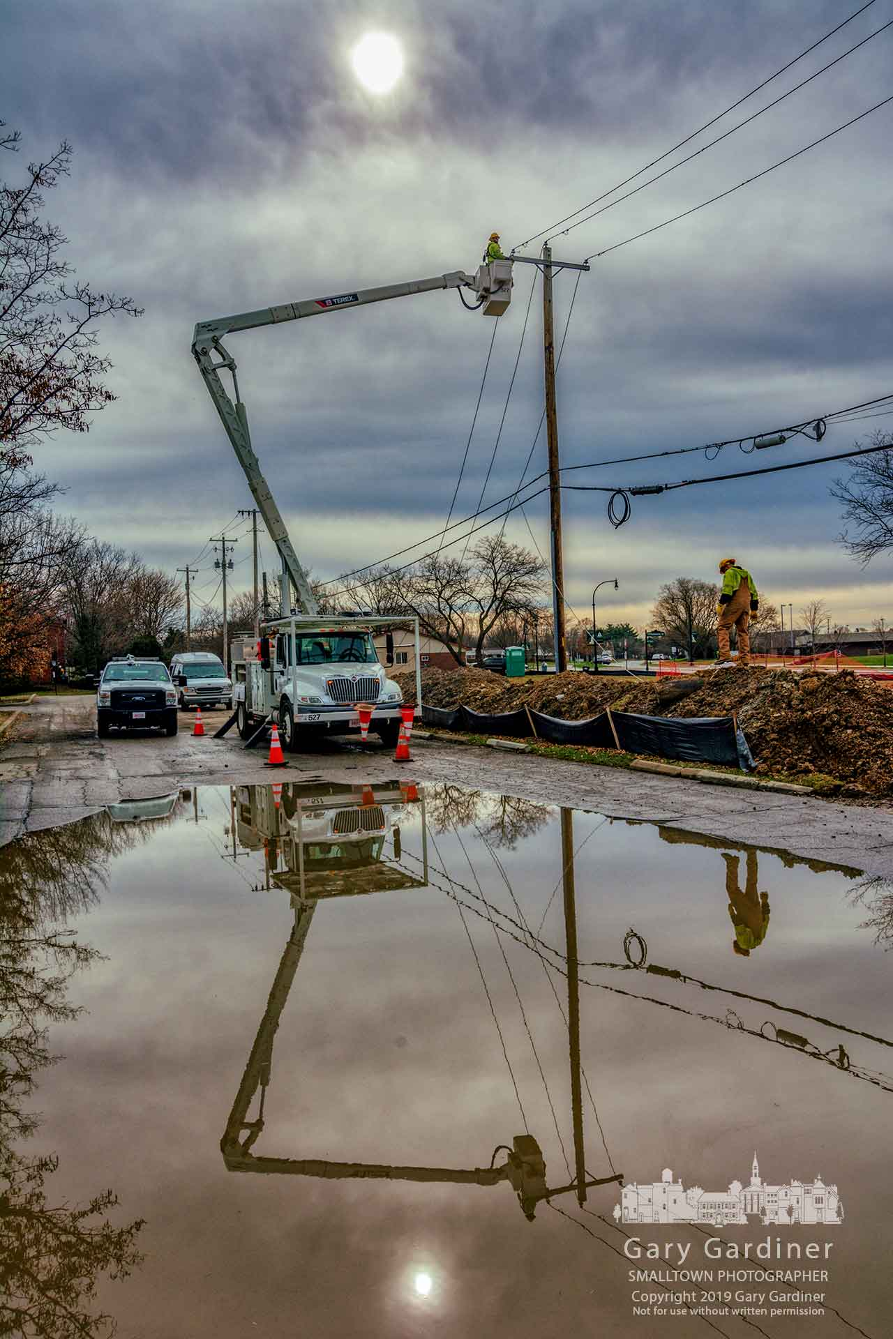City electricians reroute overhead power lines to underground conduits as construction begins on the First Watch restaurant at the corner of South State and Huber Village. My Final Photo for April 2, 2019.