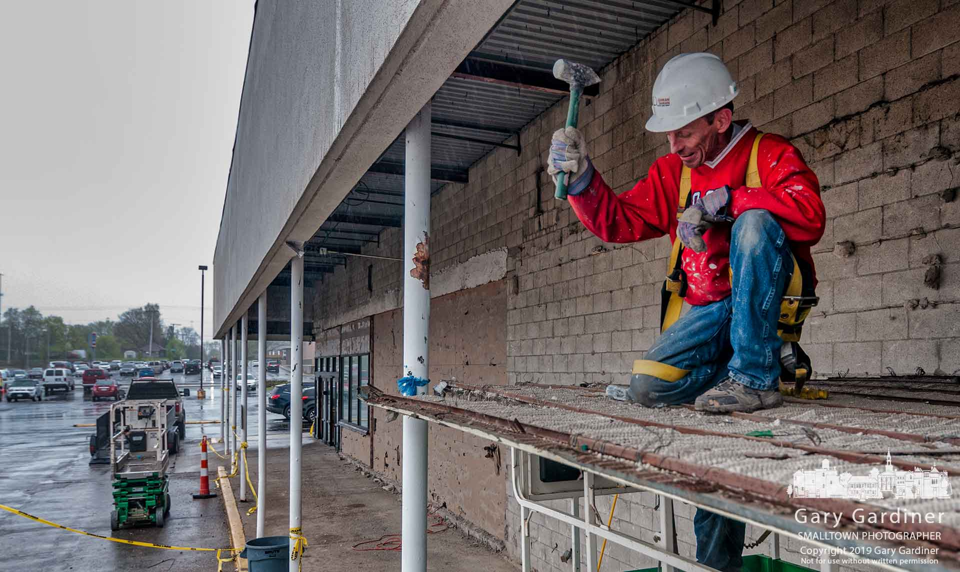 A construction worker hammers away a section of steel and stucco that made up the covering of the sidewalks at Glengary Shopping Center as work continued Friday upgrading and renovating the center. My Final Photo for April 19, 2019.