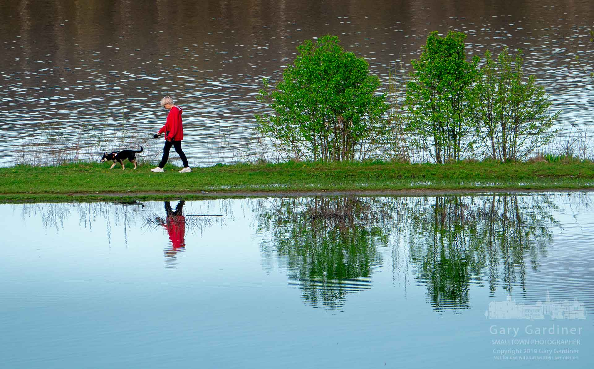 A woman walks her dog along the shoreline of Hoover Reservoir on Easter afternoon as the cloudy skies of earlier in the day cleared to provide a bright sunset. My Final Photo for April 21, 2019.