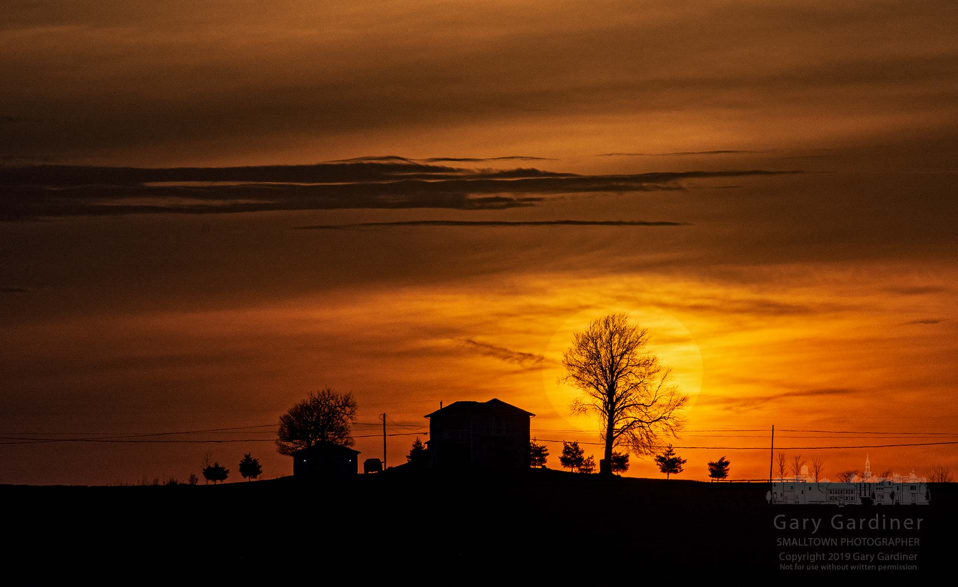 A thin cloud layer partially obscures the setting sun behind a house in farm fields near Croton, Ohio. My Final Photo for April 13, 2019.