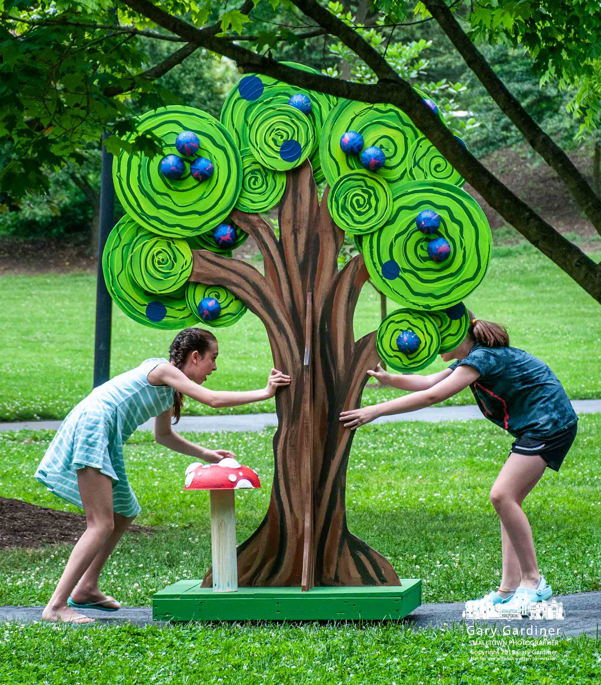 Alice in Wonderland Jr. cast members do double duty as stagehands as they move one of the set's trees toward the stage before the second performance of the Westerville Parks & Rec Civic Theatre's production at Alum Creek Amphitheater. My Final Photo for May 31, 2019.