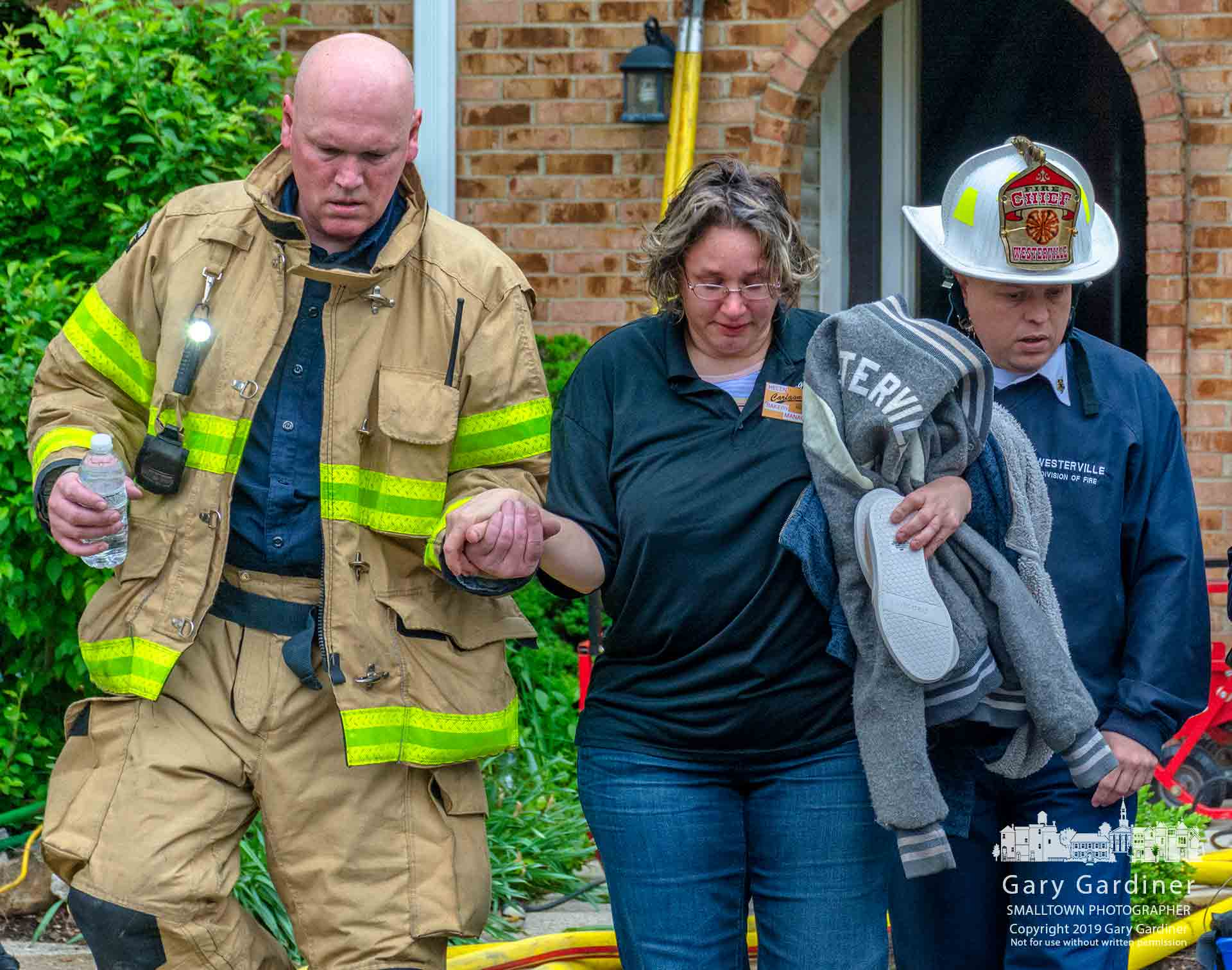 Westerville firefighters help a woman retrieve clothing from her smoke-damaged apartment after an adjacent apartment was damaged in a Saturday morning fire. My Final Photo for May 4, 2019.