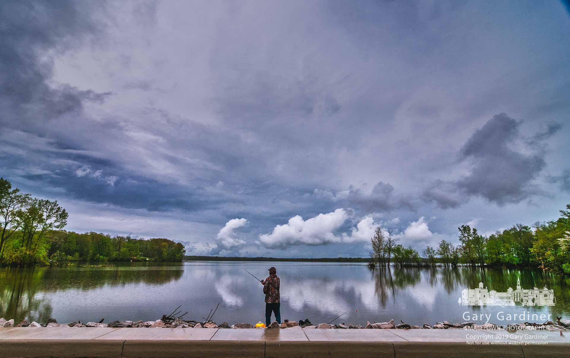 Great Day For Fishing - A fisherman casts into the waters of Hoover Reservoir on a rainy afternoon that saw few people other than those hoping for fish for dinner braving the elements at the lake. My Final Photo for May 3, 2019.