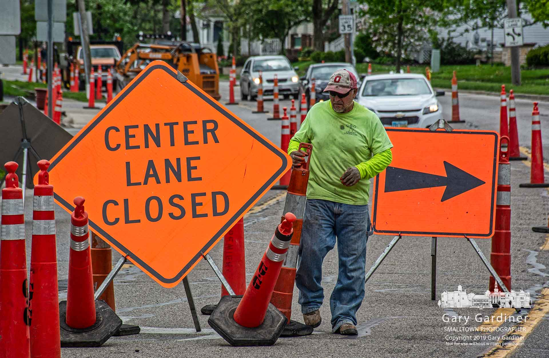 A contractor repositions cones and signs as work continues up North State Street to remove and replace curbs and gutters during the summer. My final Photo for May 1, 2019.