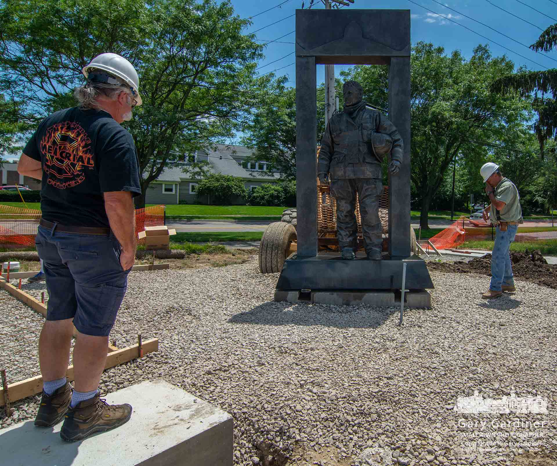 "Retired Westerville firefighter Tom Ullom watches as ""The Crossing,"" a statue dedicated to Westerville firefighter David Theisen who died in a fire, is lowered into its new location in the redesigned First Responders Park on West Main Street. My Final Photo for June 26, 2019."