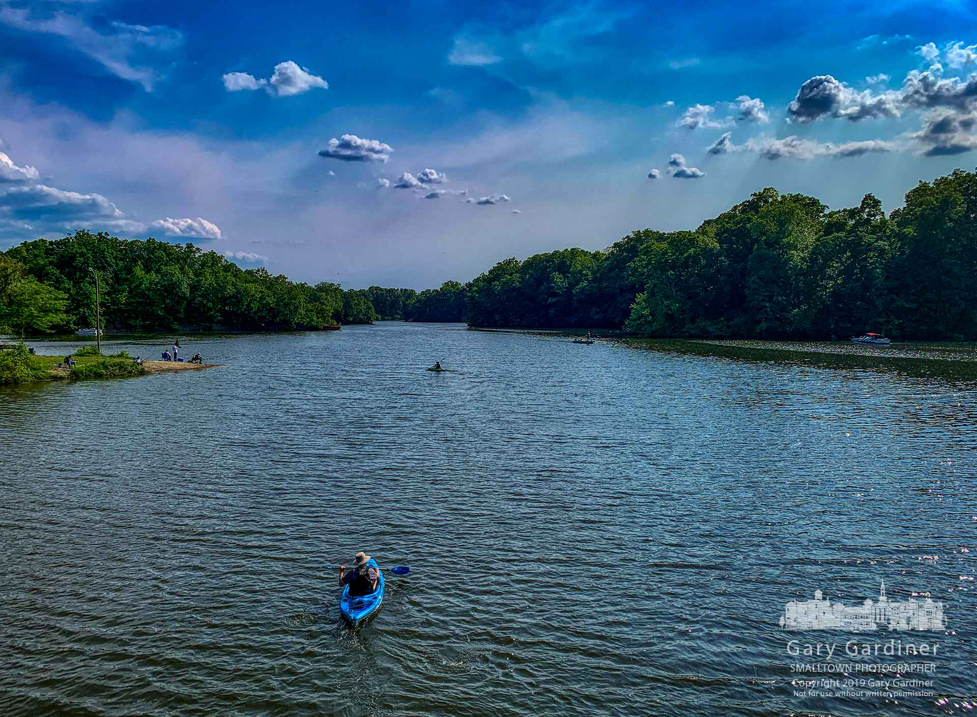 Kayakers paddle across an inlet on the northern end of Hoover Reservoir near Galena in the late afternoon sun. My Final Photo for June 1, 2019.