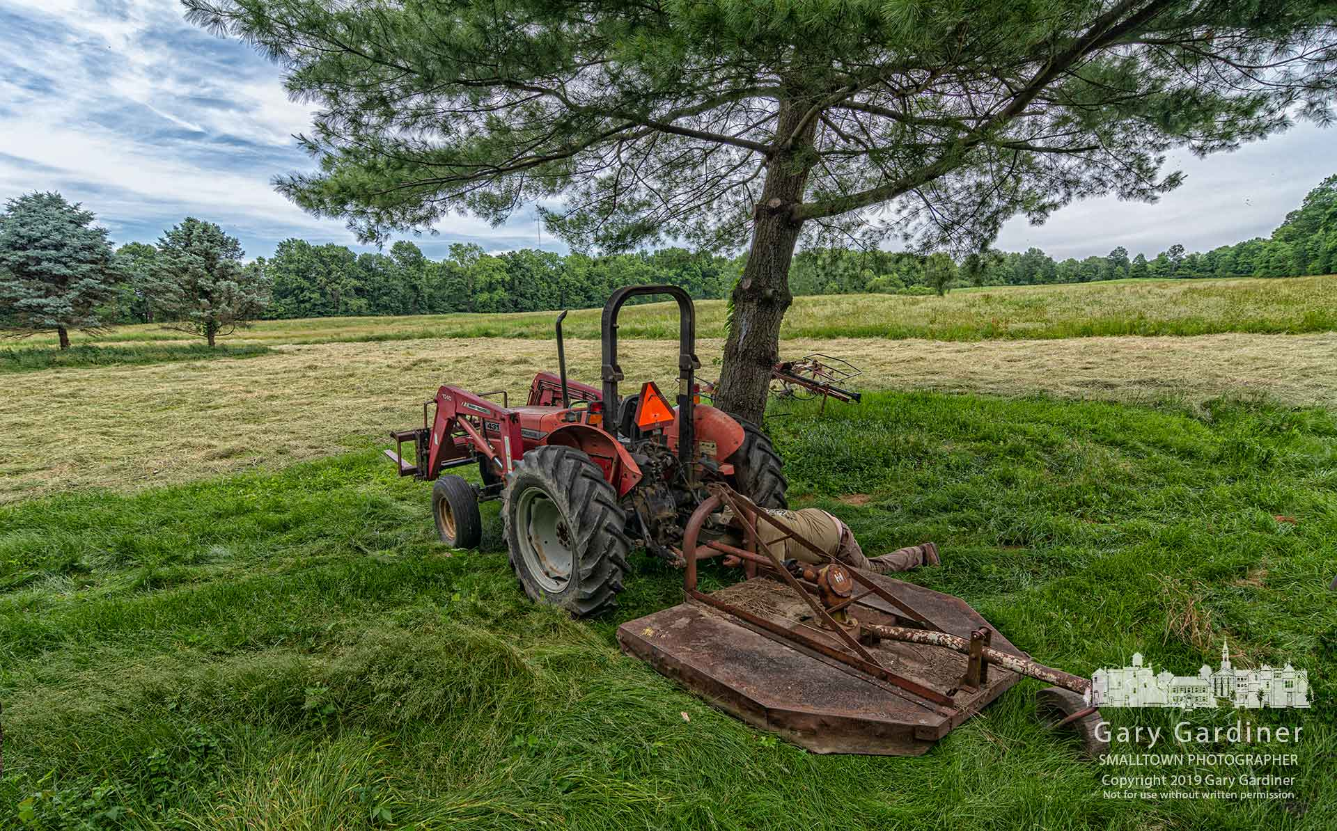Farmer Kevin Scott attaches a bush hog to his tractor as he prepares to cut the grass around the Sharp Home and hay field on Africa Road. My Final Photo for June 7, 2019.