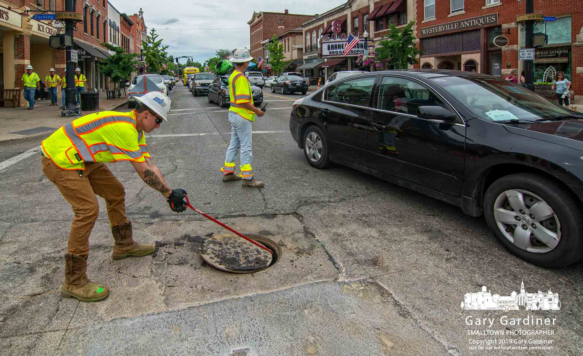 A pipeline crew worker pulls away a manhole cover at State and College to unjam a camera lodged in a sewer line during inspection before the company begins boring for a new Columbia Gas pipeline beneath State Street. My Final Photo for June 12, 2019.