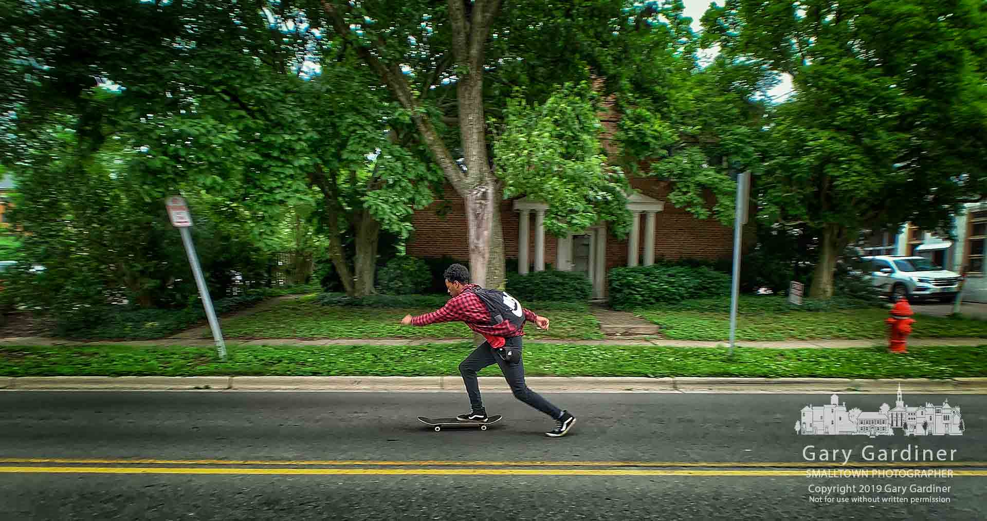 A skateboarder thrusts himself down West Main Street against a strong afternoon wind. My Final Photo for June 14, 2019.
