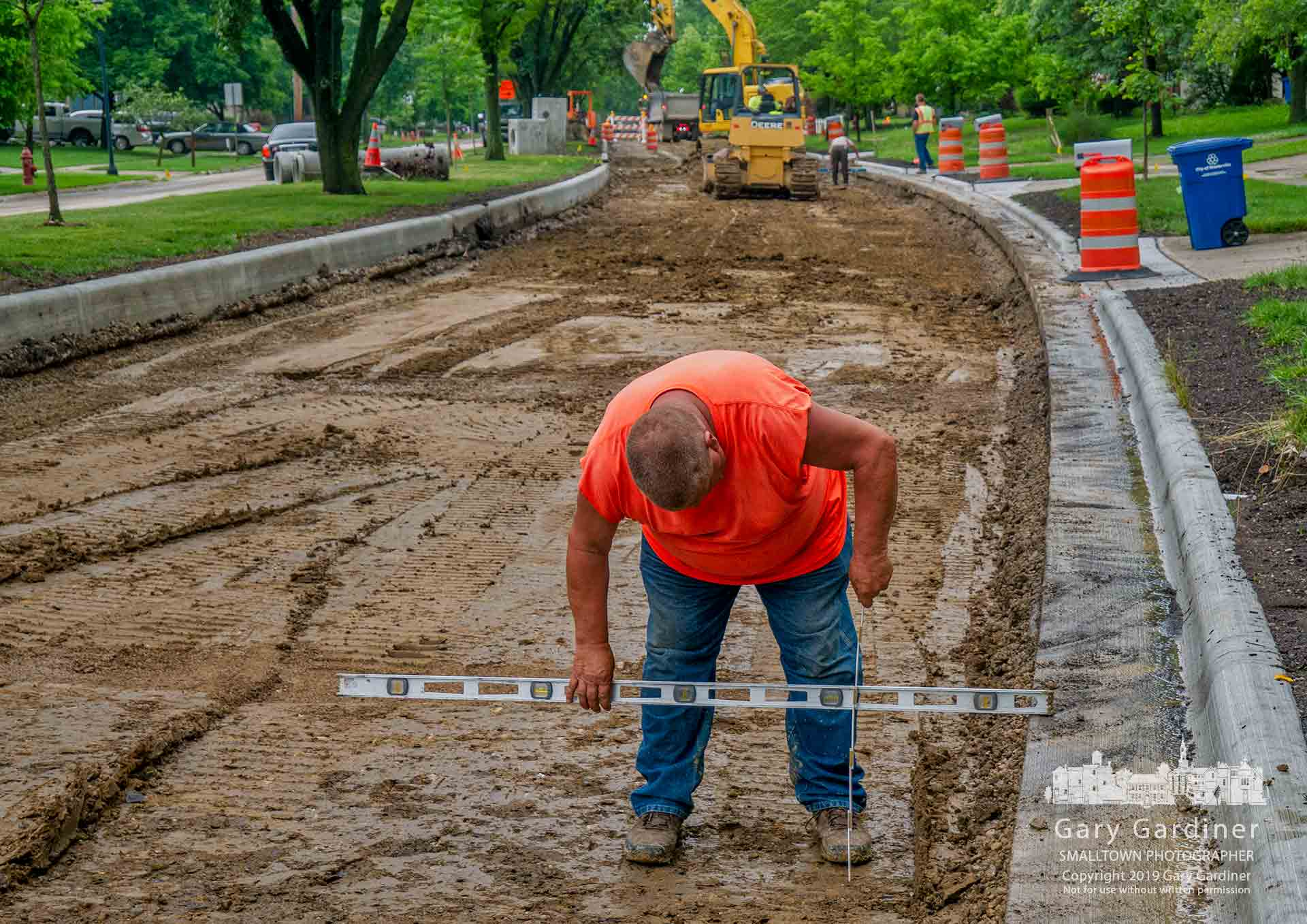 A concrete crew supervisor checks the depth below the gutters of Spring Road as the crew prepares to add a concrete and gravel underlay before laying a level of asphalt to complete a section of the street near Schrock. My Final Photo for June 19, 2019.