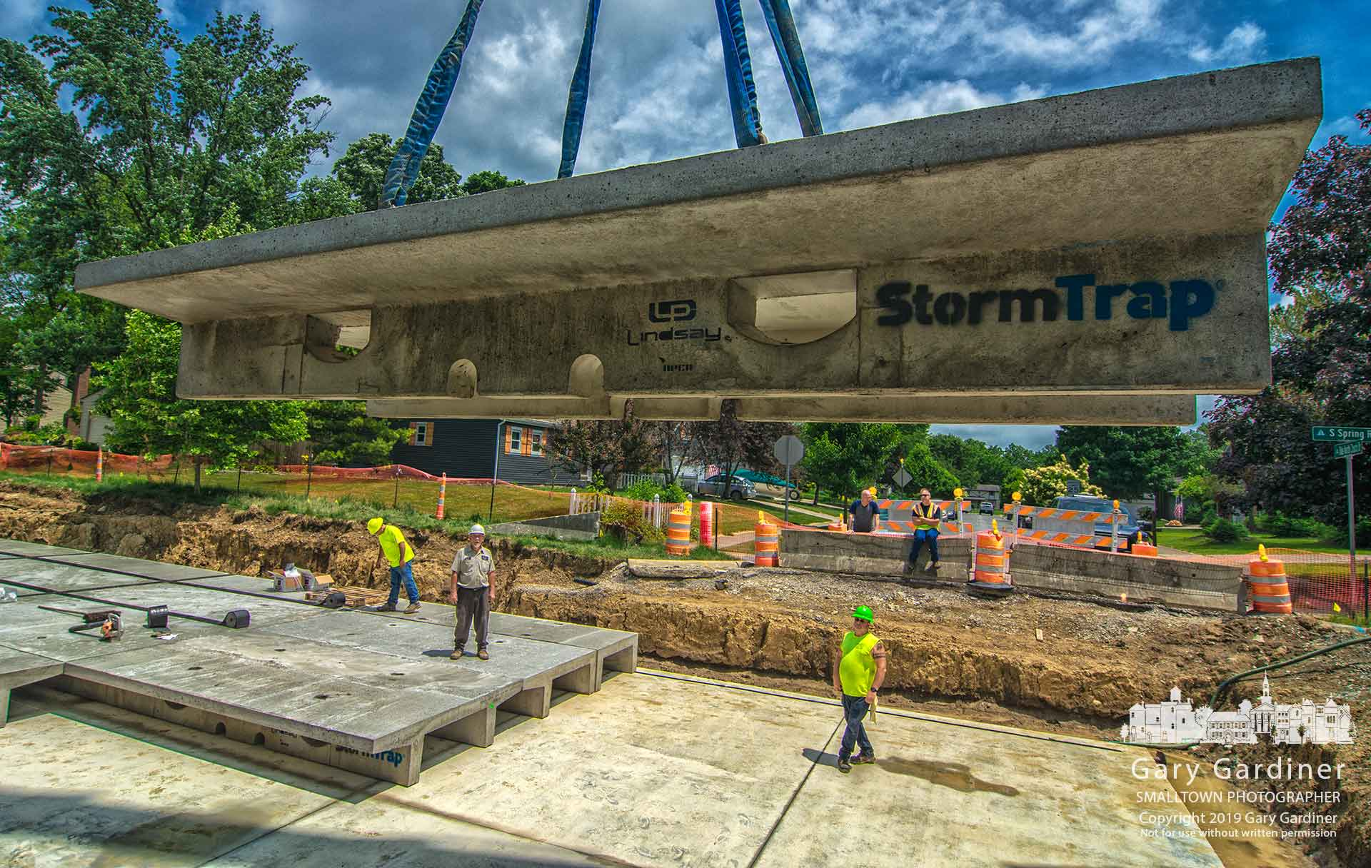 A concrete storm drain baffle is lowered into place on Spring Road as contractors near completion of the first of four underground temporary storage systems designed to regulate heavy runoff along Spring. My Final Photo for June 5, 2019.