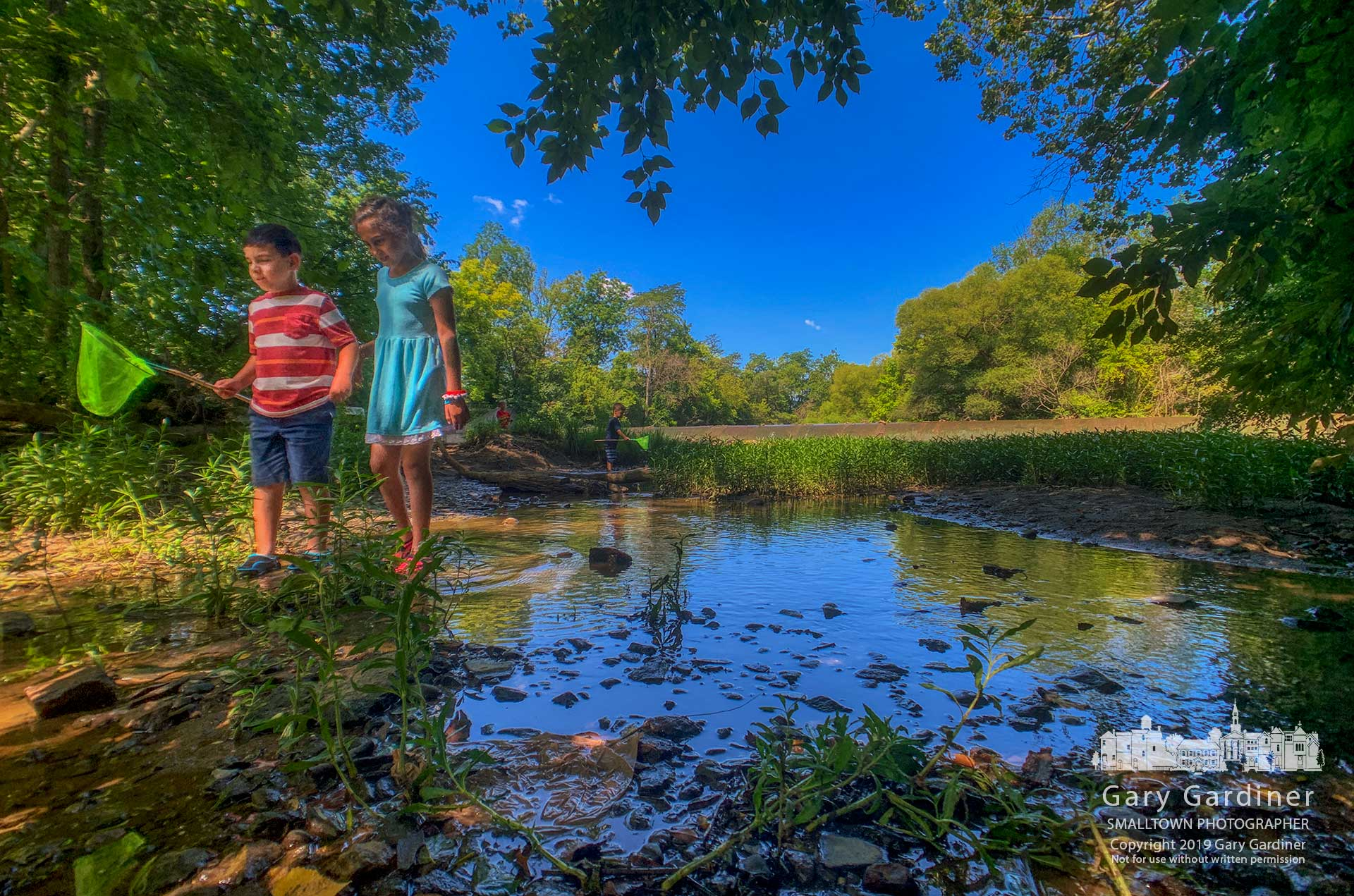 A brother and sister head downstream searching for minnows to add to their father's catch from fishing below the lowhead dam in Alum Creek Park North in Westerville. My Final Photo for July 25, 2019