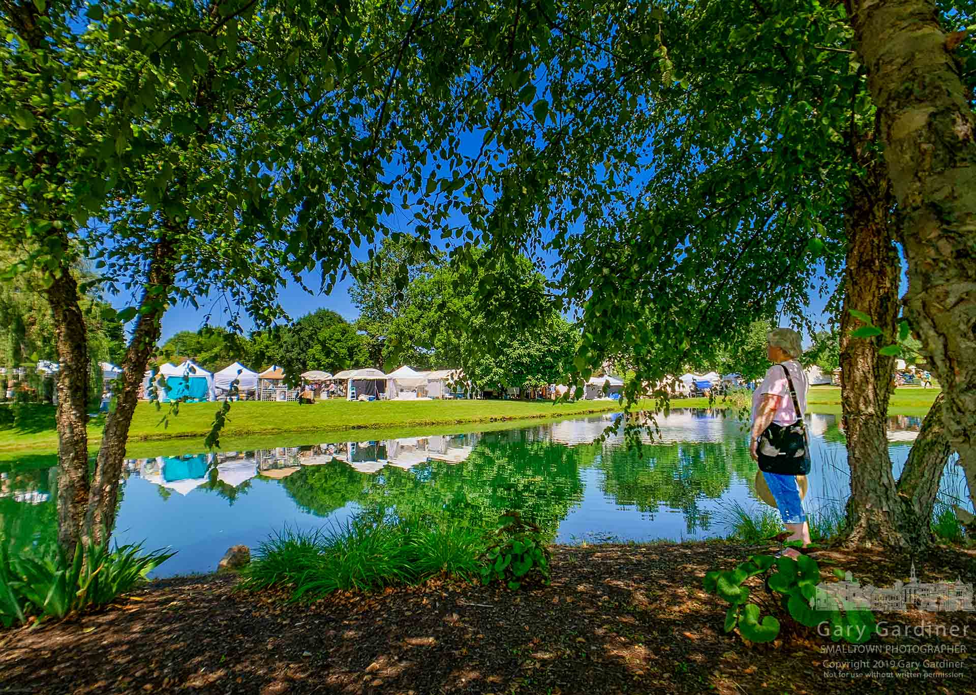 A few of the artist's tents at the Westervlle Music & Arts Festival are reflected in the main pond as the two-day festival opened Saturday morning at Heritage Park. My Final Photo for July 13, 2019.