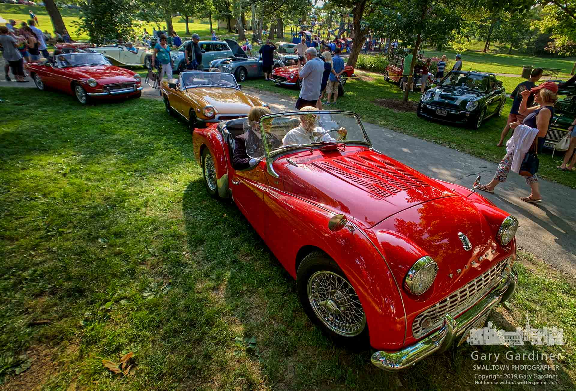 A red Triumph Roadster leads the line of British sports cars taking The British Invasion to the stage at the Alum Creek Amphitheater where the group performed popular British songs from the 60s and 70s. My Final Photo for July 14, 2019.