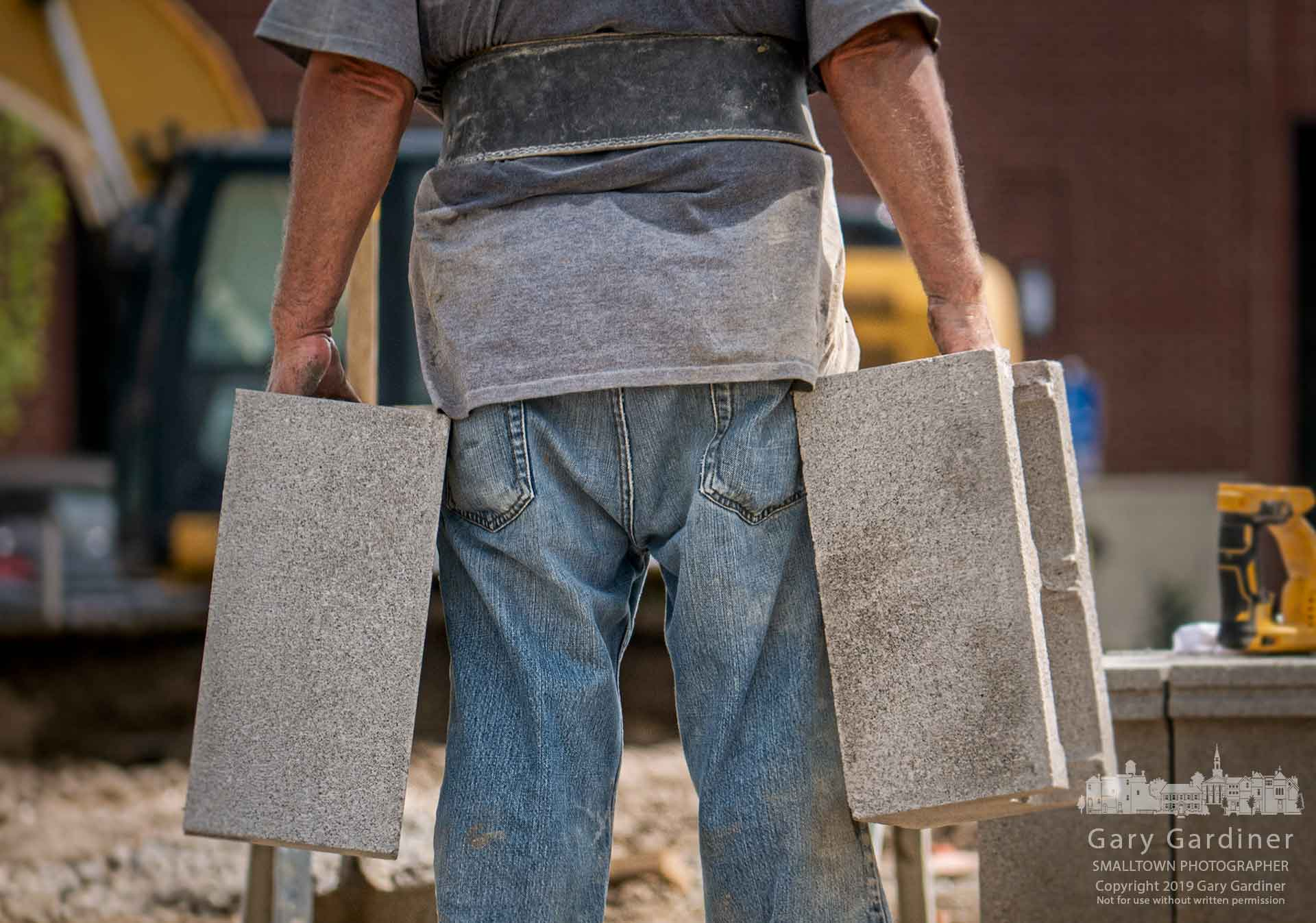 A worker carries concrete blocks across the site where his team is building the foundation for a new set of restaurants at Polaris Parkway and Meridian Way. My Final Photo for July 18, 2019.