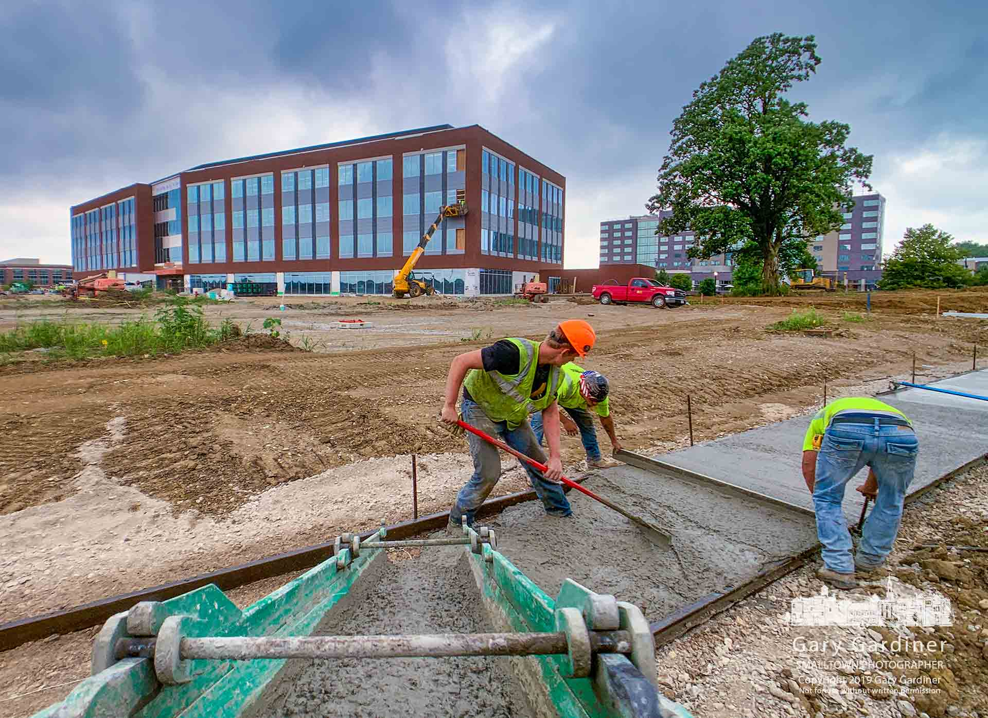 Workers pour a section of sidewalk around the edge of what will become the parking for DHL's new North and South America headquarters building nearing completion in the Westar development area. My Final Photo for July 30, 2019.