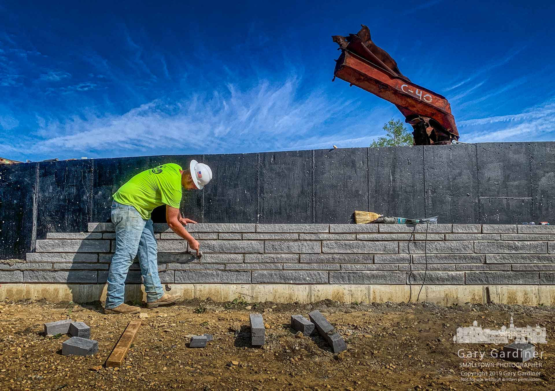 A brick mason uses a joint raker to set mortar into a section of the decorative wall being built at the front of Responders Park. My Final Photo for July 11, 2019.