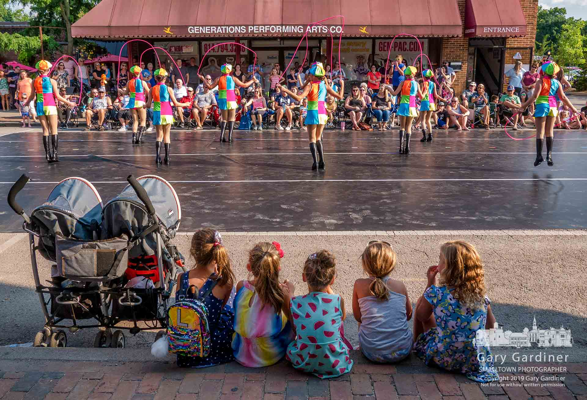 A group of young girls watch from the curb as an older group dances on West College during the Fourth Friday street festival in Uptown Westerville. My Final Photo for July 26, 2019.