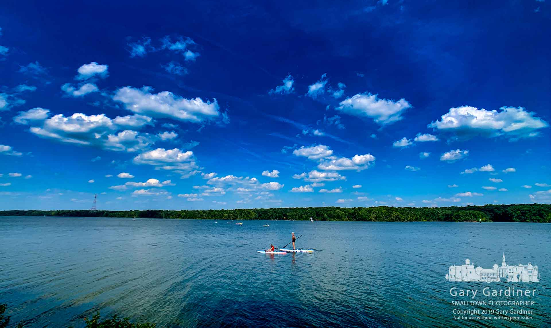 A mother and daughter navigate their paddleboards back to the shore at Hoover Reservoir under a deep blu sky with light cumulous cloud cover on a warm late July afternoon. My Final Photo for July 27, 2019.