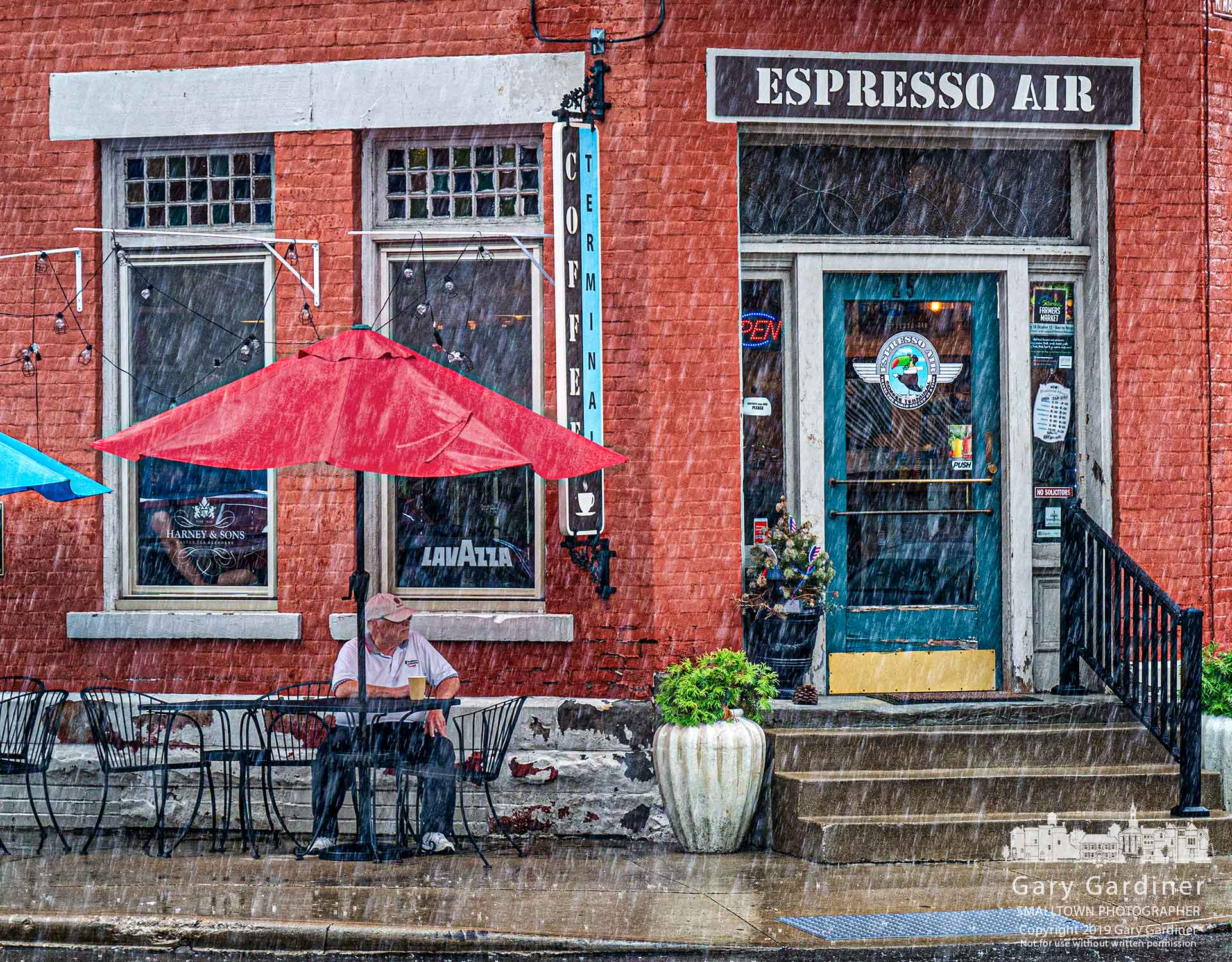 Uptown Dave with his coffee and cigar takes refuge from an afternoon rainstorm on the leeward side of the Holmes Hotel at State and Main in Uptown Westerville. My Final Photo for July 17, 2019.