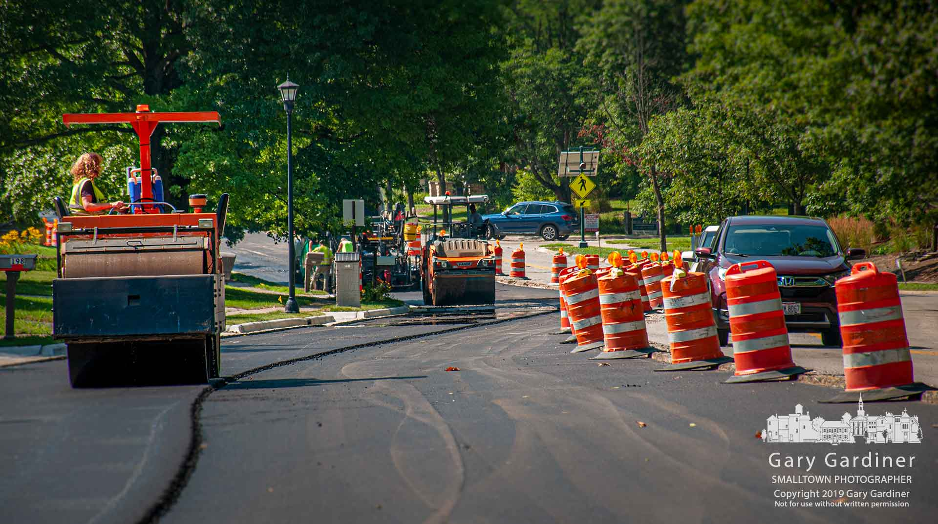 A steamroller compacts fresh asphalt laid on the end of the northbound lanes of Spring Road as the project prepares to switch traffic to the completed section and begin rebuilding the southbound lanes on Monday. My Final Photo for July 20, 2019.