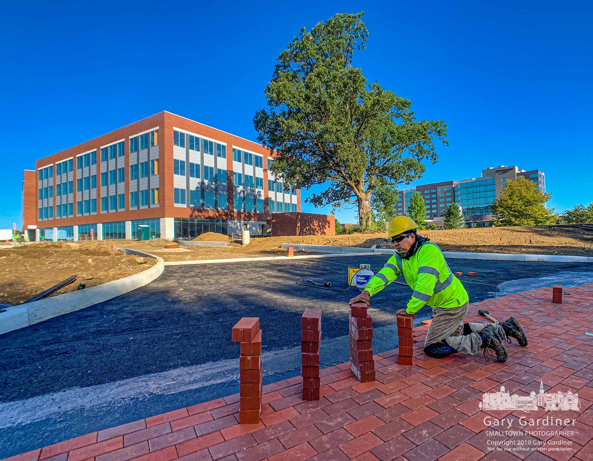 A bricklayer places pavers at an entrance to what will be the parking lot for the new DHL Logistics North and South America headquarter building. My Final Photo for Aug. 29, 2019.