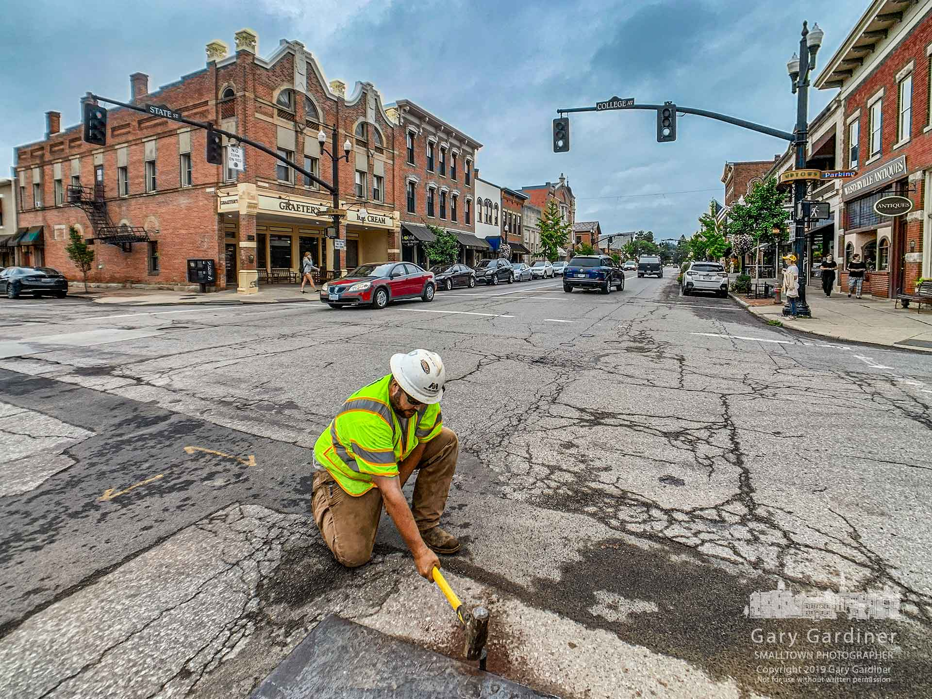 A Miller Pipeline worker hammers a railroad spike into State Street to hold the edge of a steel plate laid in the street to cover a hole where the company is connecting new gas lines. My Final Photo for Aug. 27, 2019.