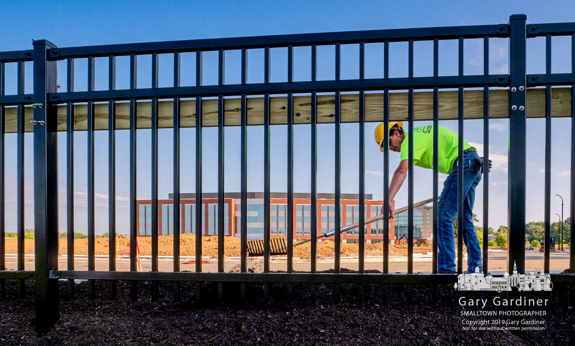 A landscaper levels dirt placed along the iron fence built at the southern edge of the new DHL Logistics headquarters building parking lot and access road. My Final Photo for Aug. 8, 2019.