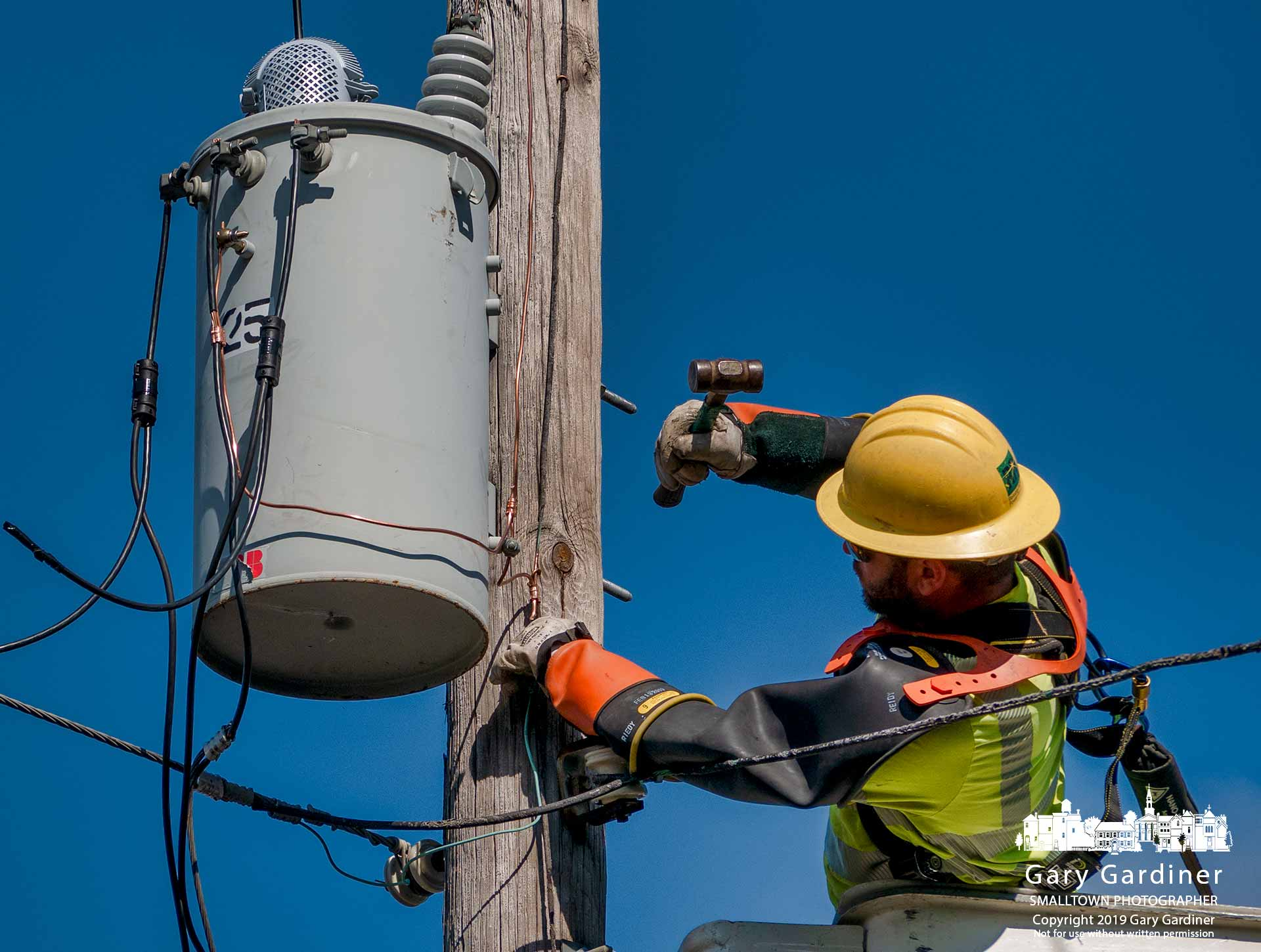 A city electric division lineman hammers in staples hold a ground wire to a utility pole on State Street after replacing an old transformer. My Final Photo for Aug. 19, 2019.