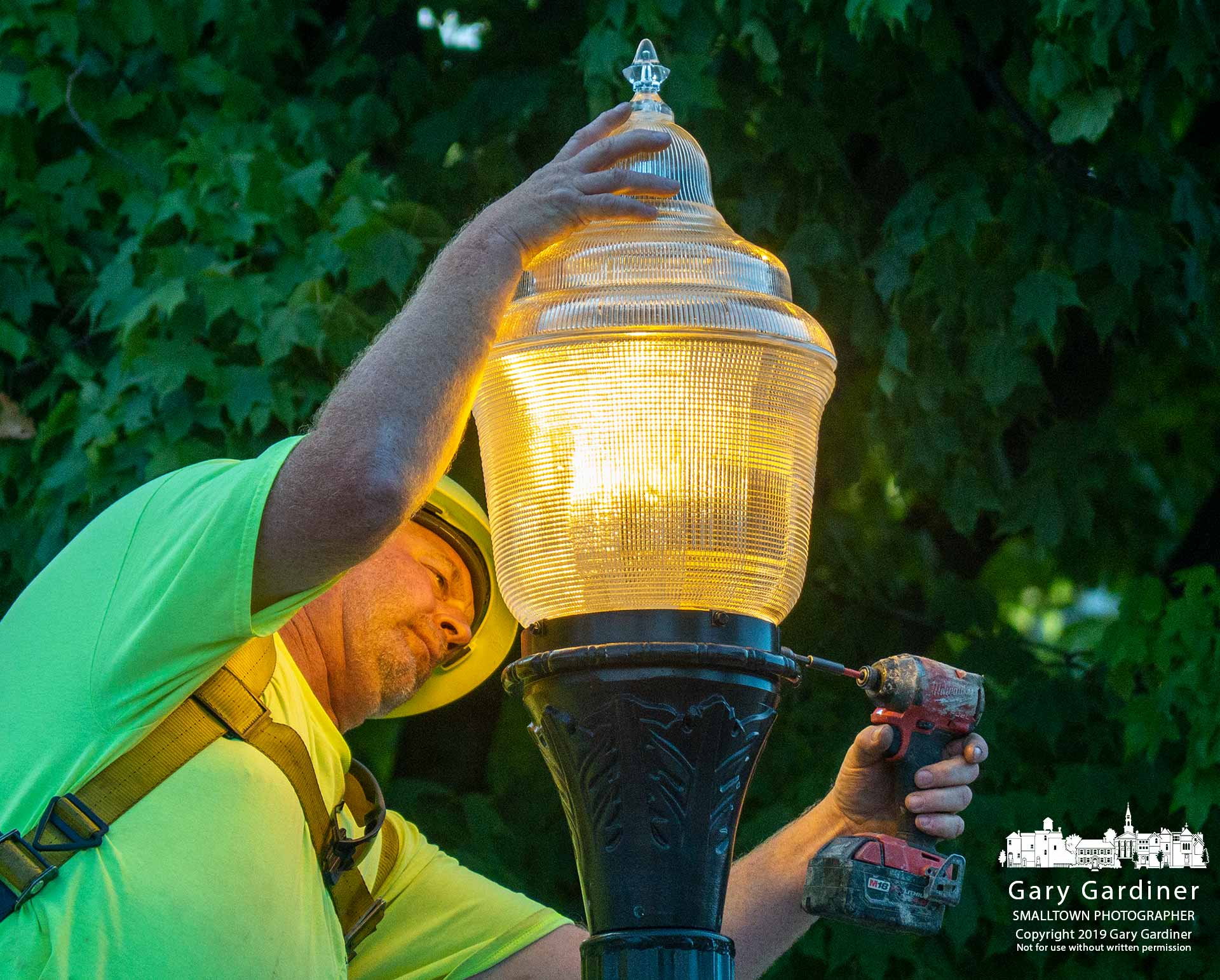 An electrician tightens screws on the mount for the glass globe placed atop the light fixture at the corner of Hanby Elementary where the sidewalk and lights were finished being replaced before school started on Tuesday. My Final Photo for Aug. 12, 2019.