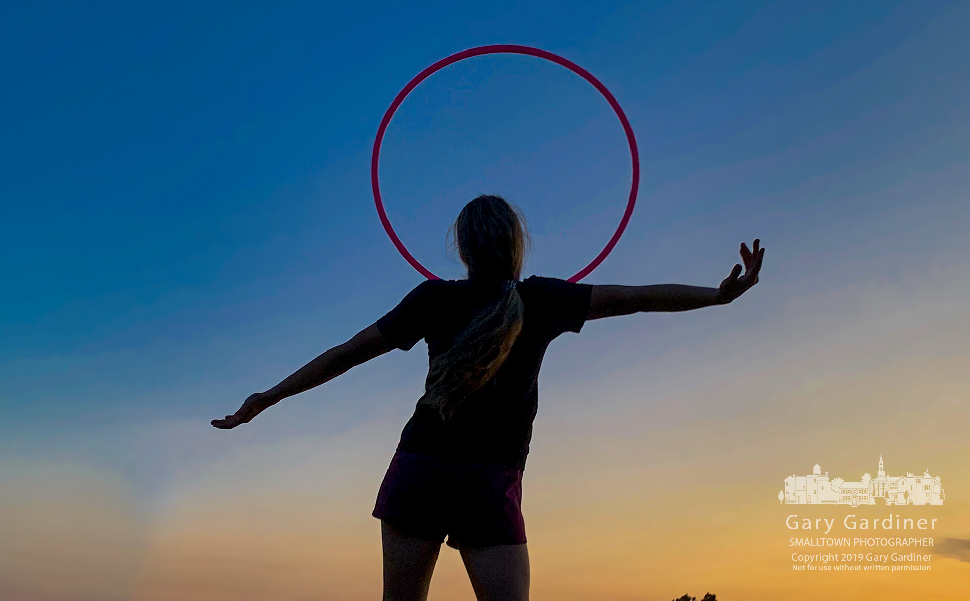 A young woman exercises with a hoop at sunset on the east end of Hoover Dam. My Final Photo for Aug. 15, 2019.
