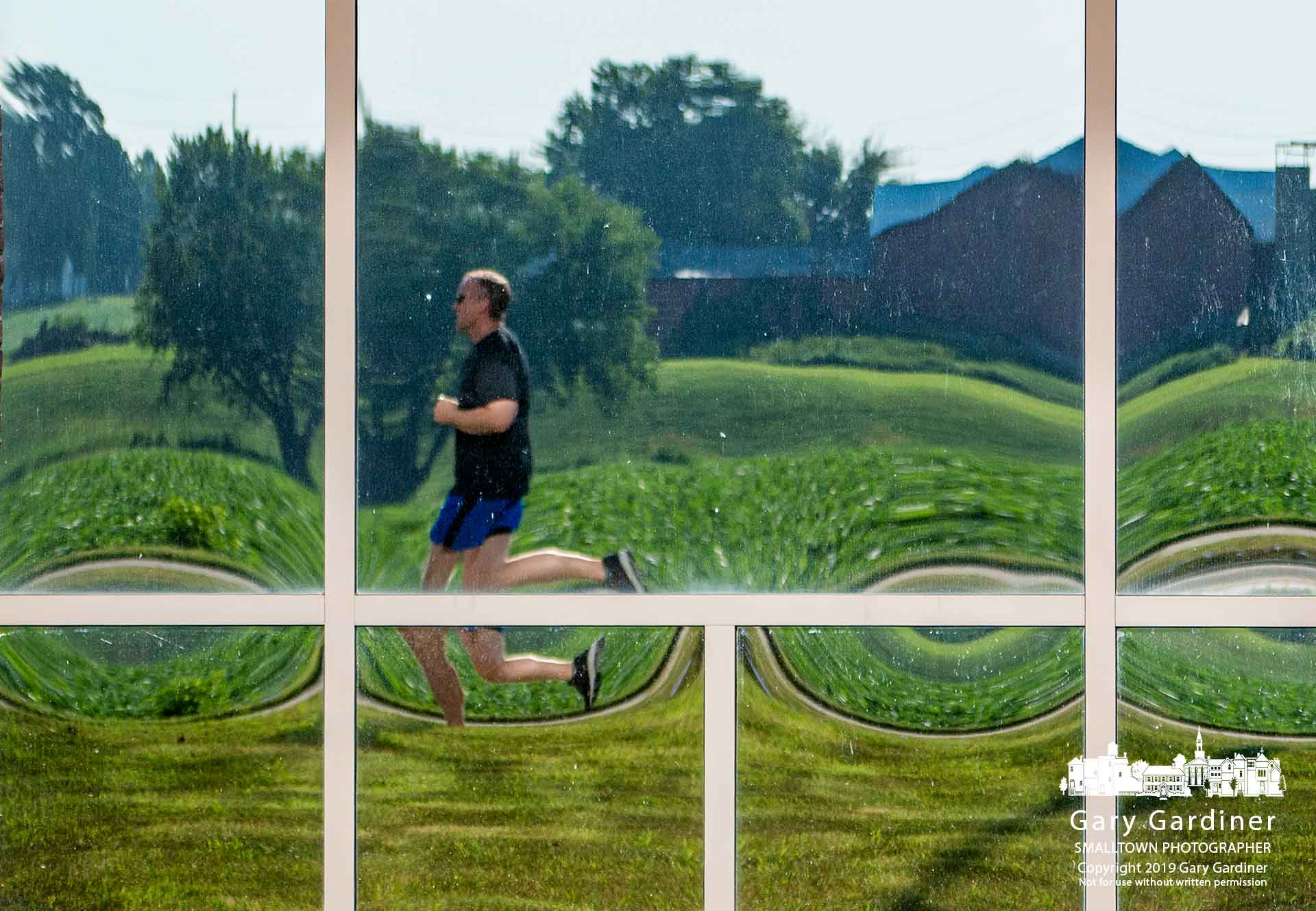 A runner and the Yarnell Farm fields and barn are reflected in the Mac Tools office building as he runs along Cleveland Ave. in early morning. My Final Photo for Aug. 3, 2019.