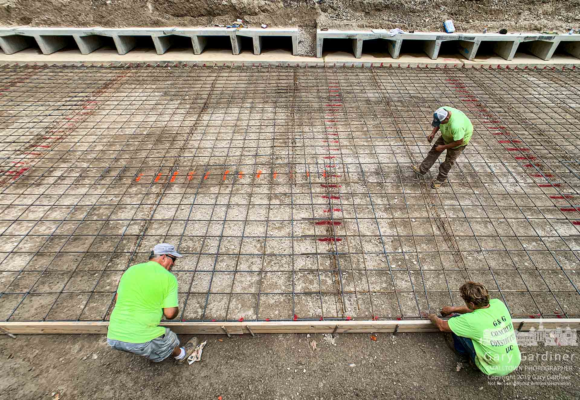 Workers tie off sections of reinforcing rebar into what will be the concrteflooring for the section section of the storm water runoff holding tank beneath Spring Road at Lincoln. My Final Photo for Aug. 21, 2019.