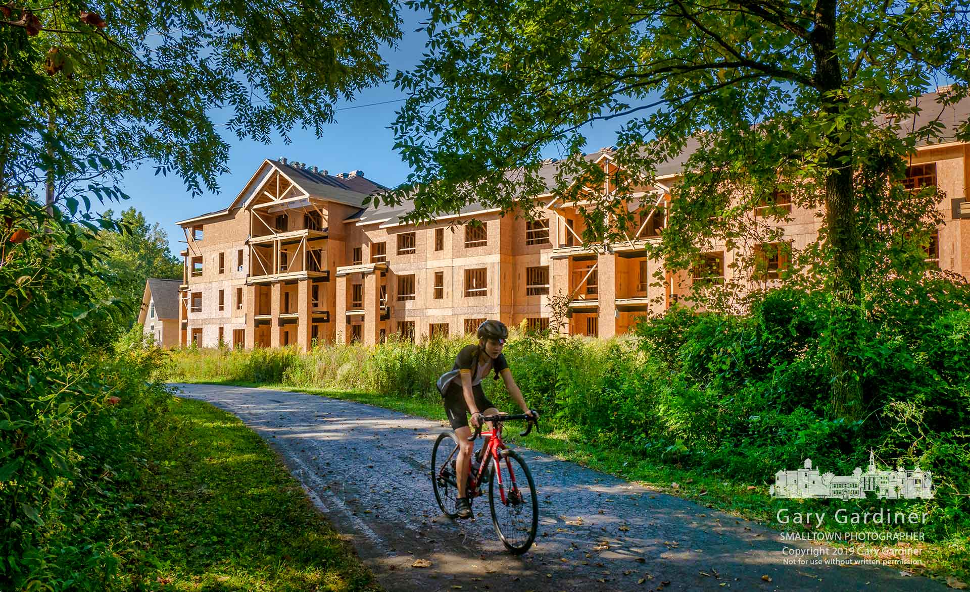 A bicyclist travels along a section of the Alum Creek bike path past a section of the apartments being built between the path and Cooper Road. My Final Photo for Sept. 18, 2019.